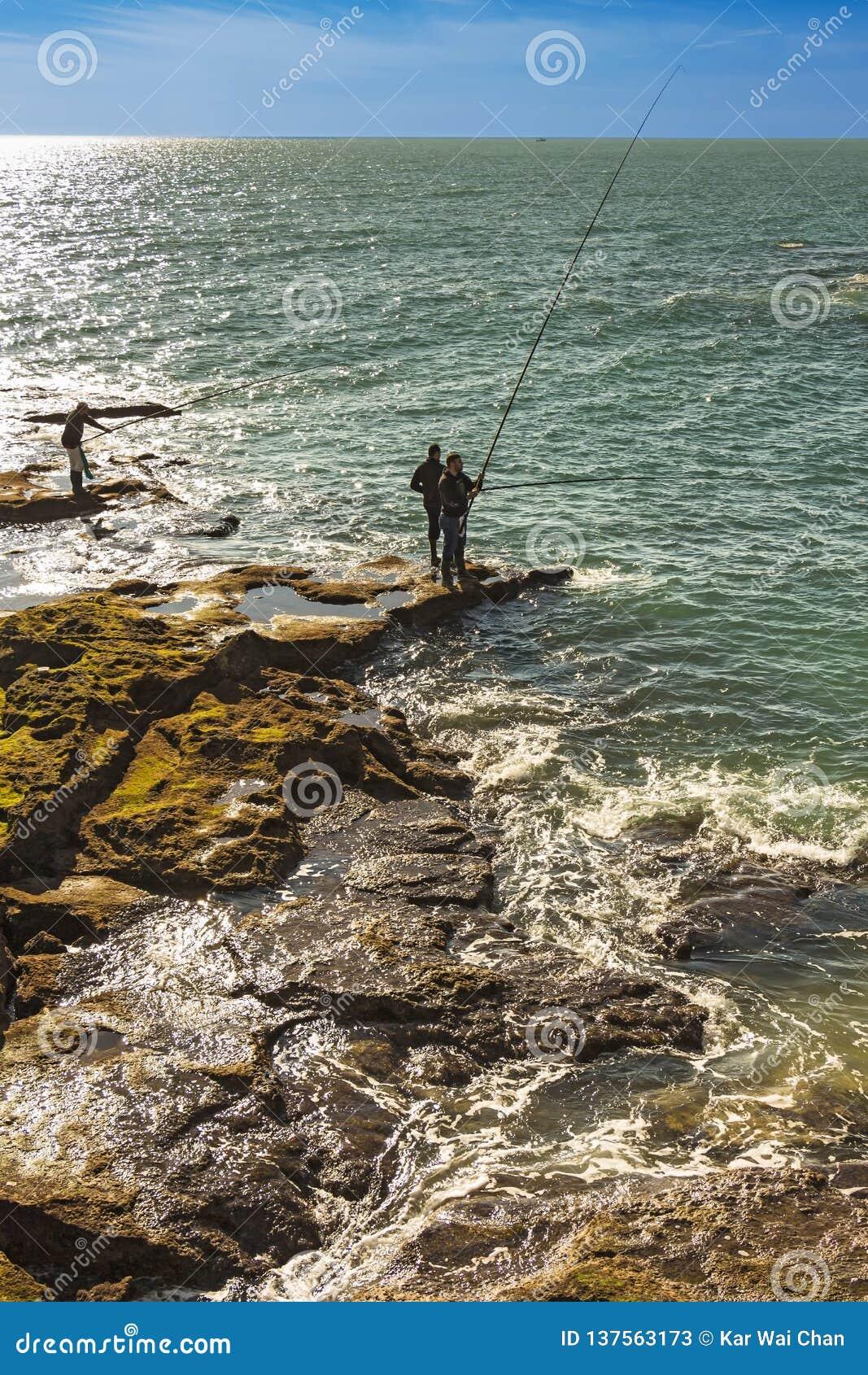 Homens que pescam fora das rochas de Paseo Fernando Quinones em Cadiz