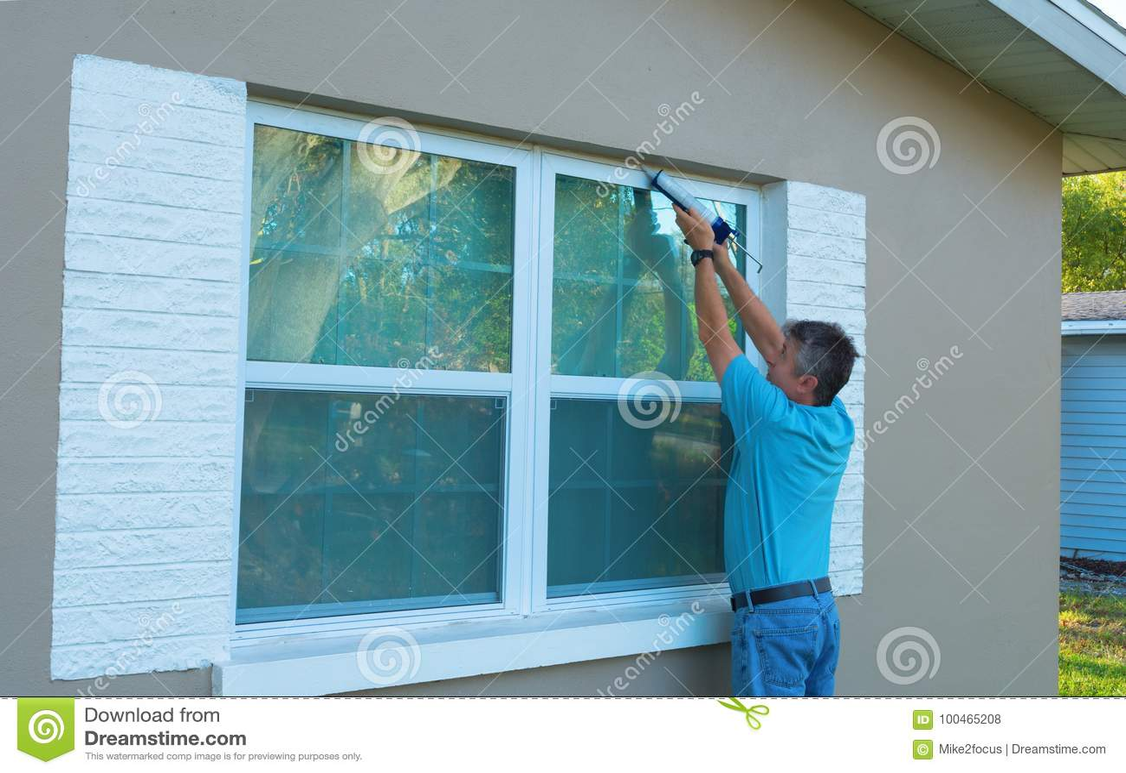 Homeowner caulking window weatherproofing home against rain and storms