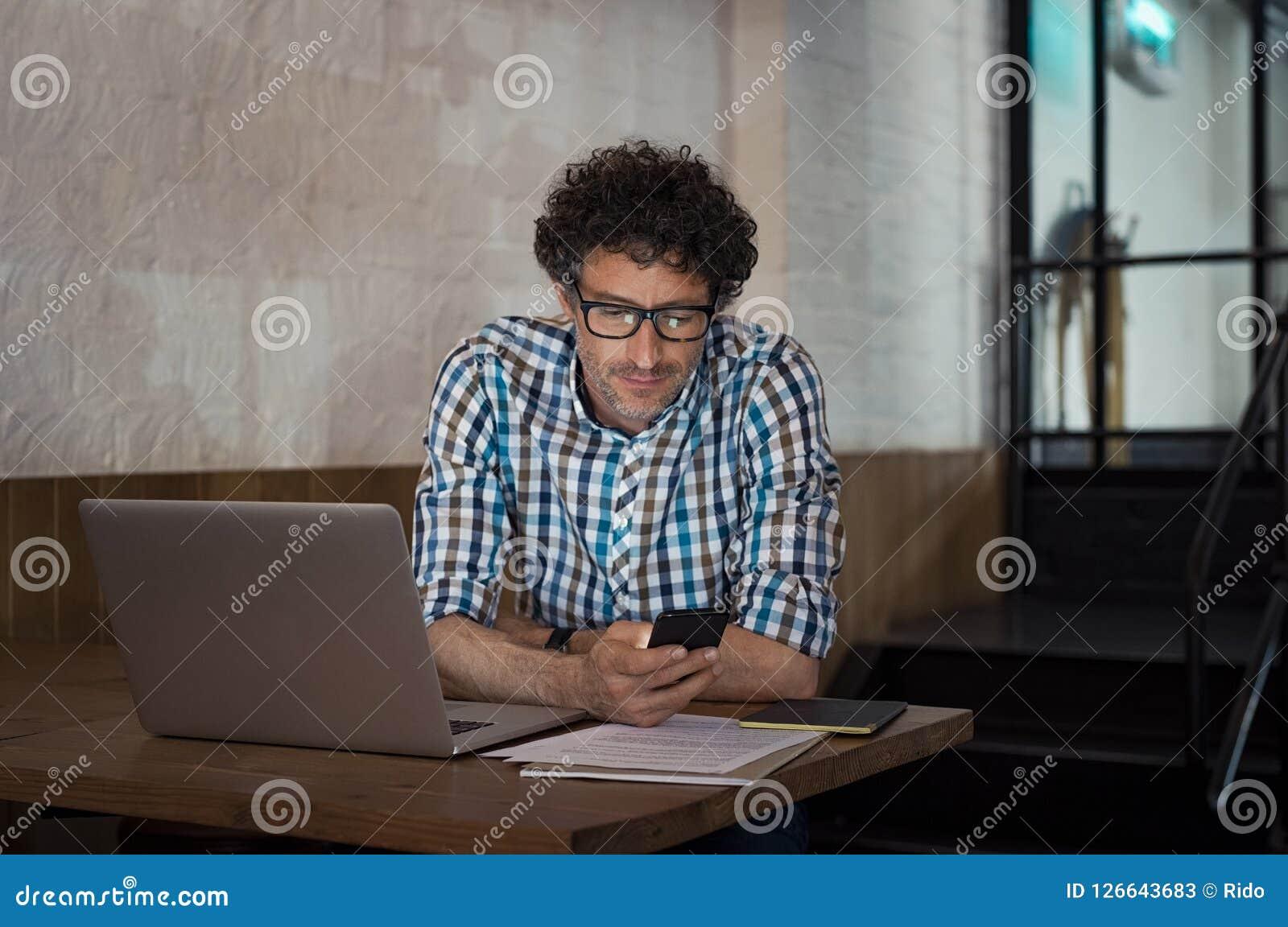 Homme à l aide de l ordinateur portable et du smartphone au café