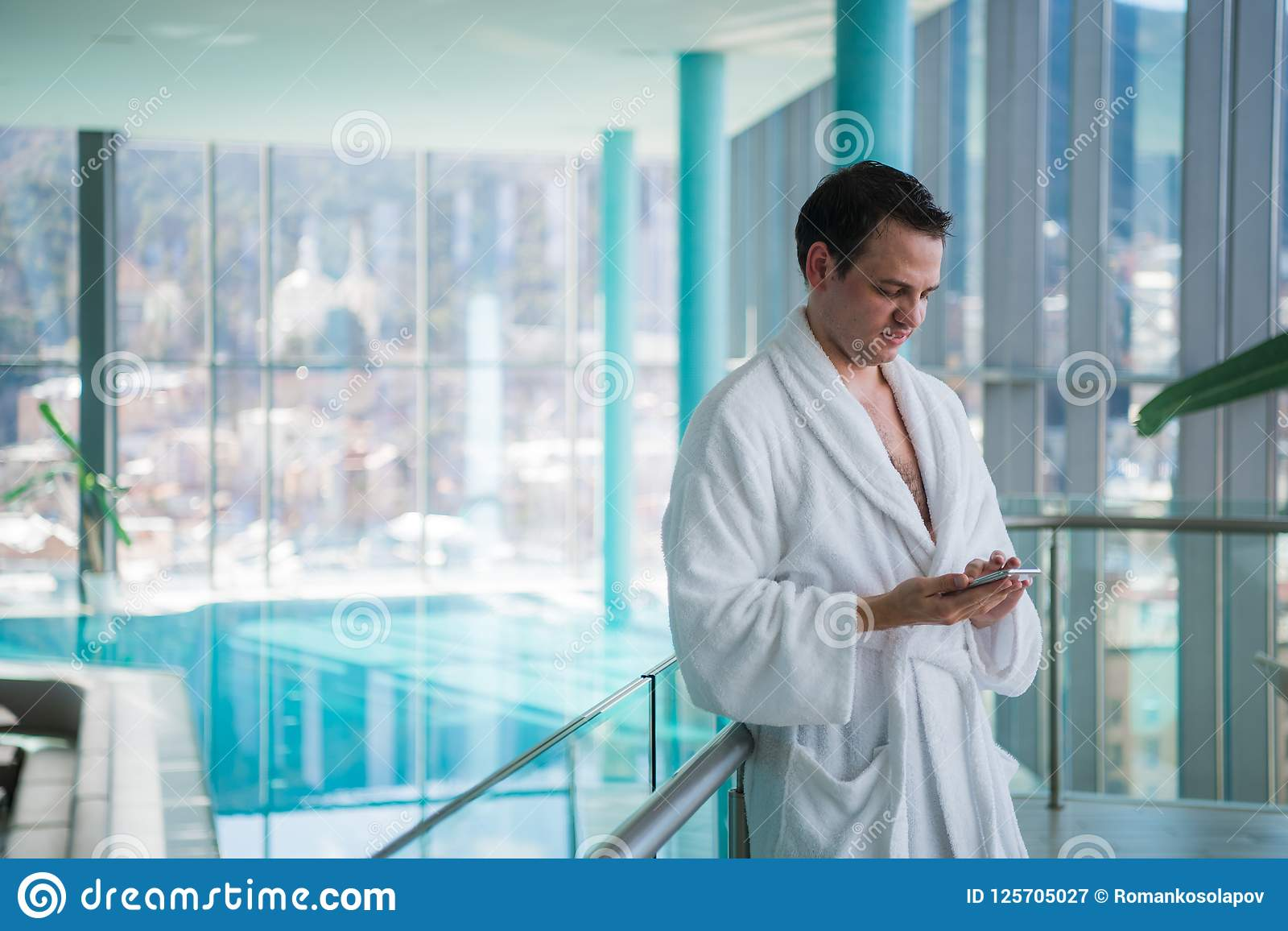 Homme à l aide du téléphone portable près de la piscine d intérieur