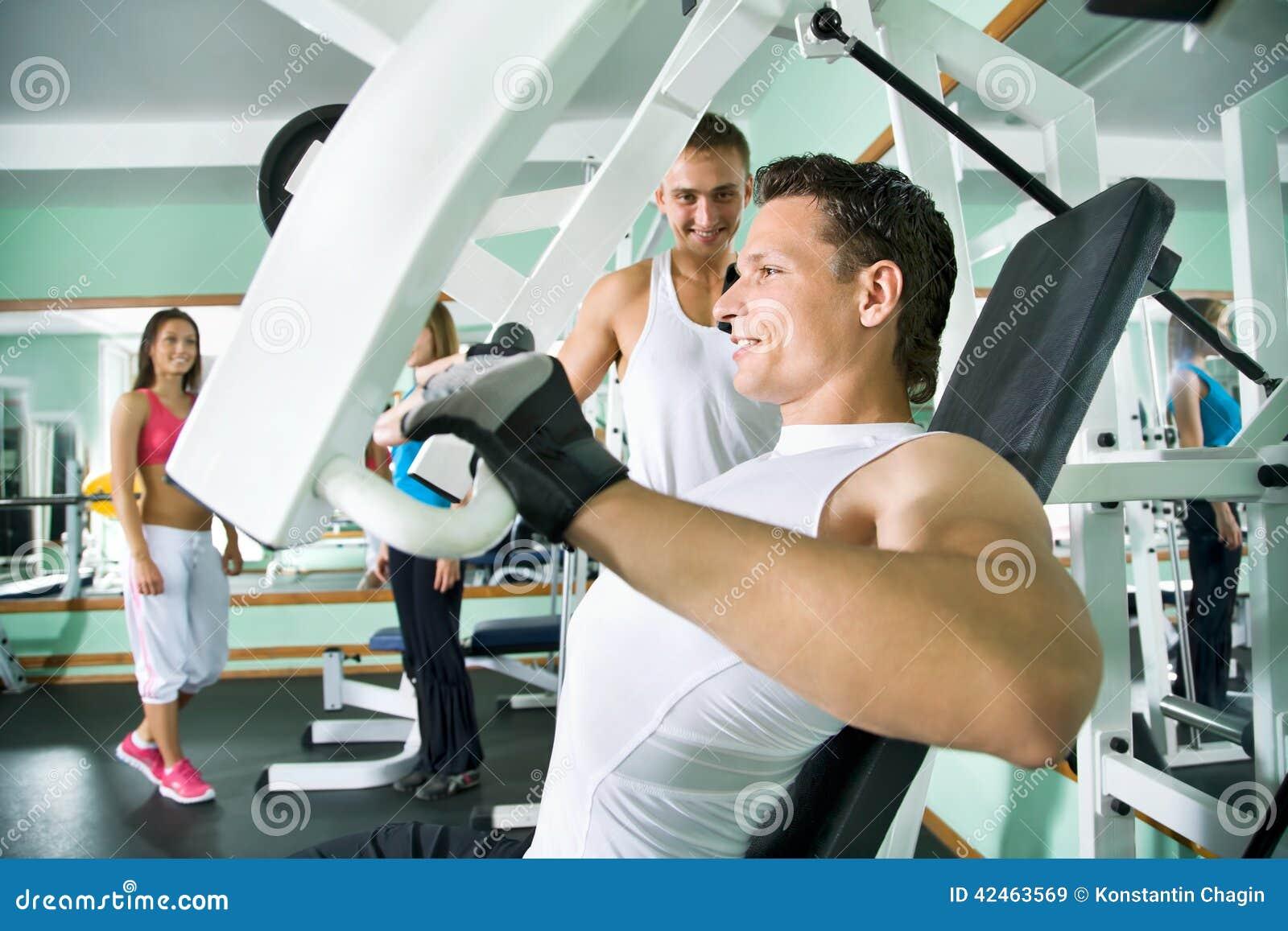 Forme physique Hommes de Yung au gymnase faisant des exercices de bras sur  une machine 98bf31690dd