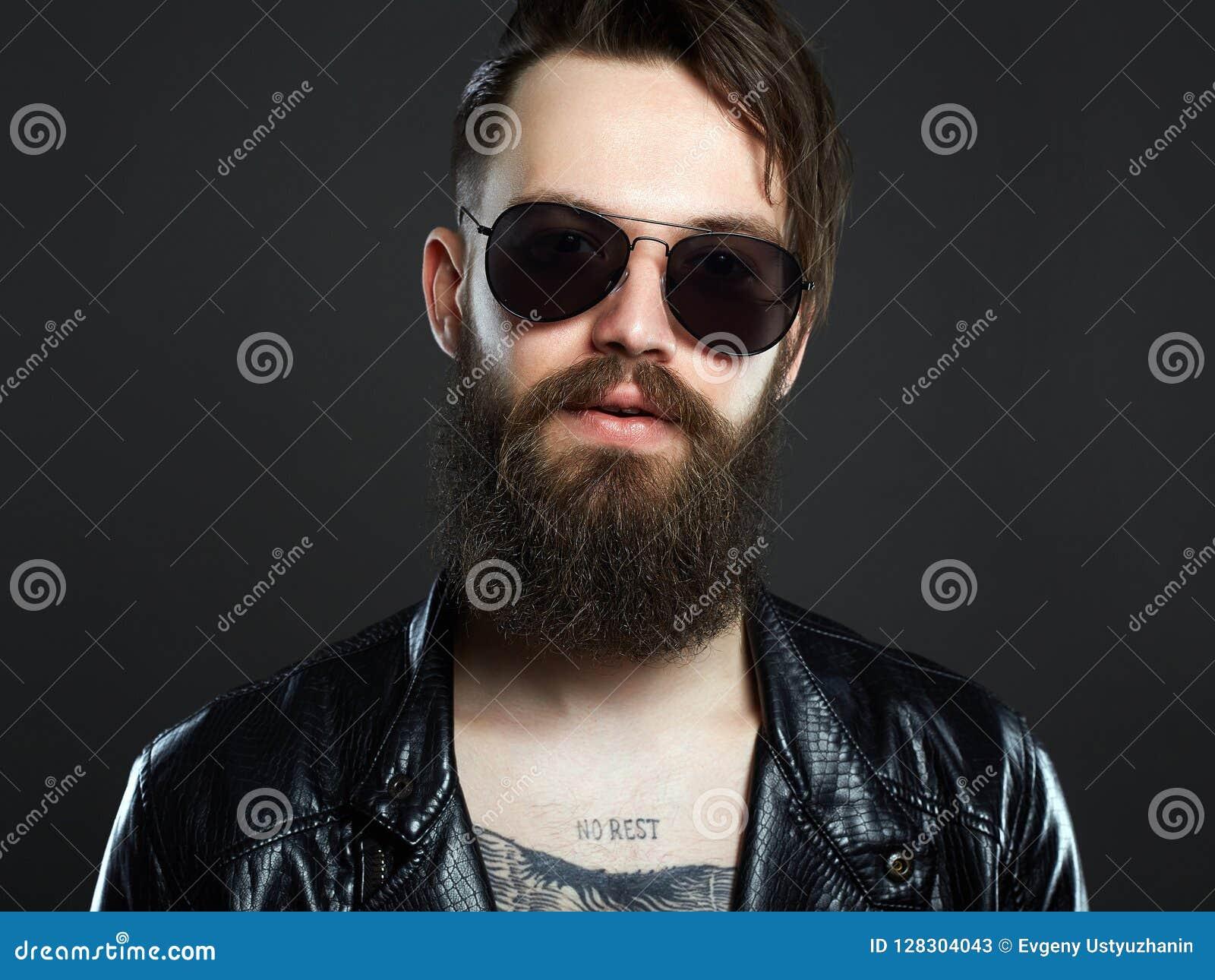 f1a7a9855e881 Homme à la mode avec le tatouage et les lunettes de soleil Garçon barbu  élégant de hippie