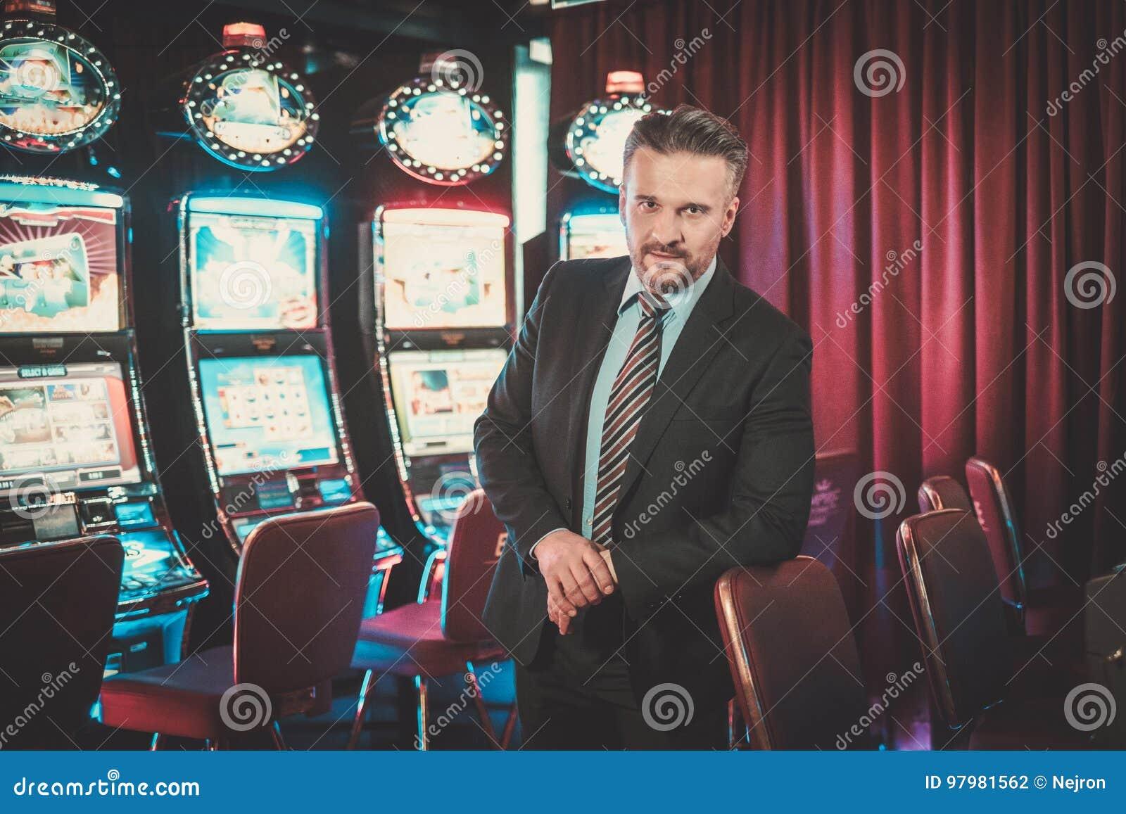 Homme élégant près des machines à sous dans un intérieur de luxe de casino