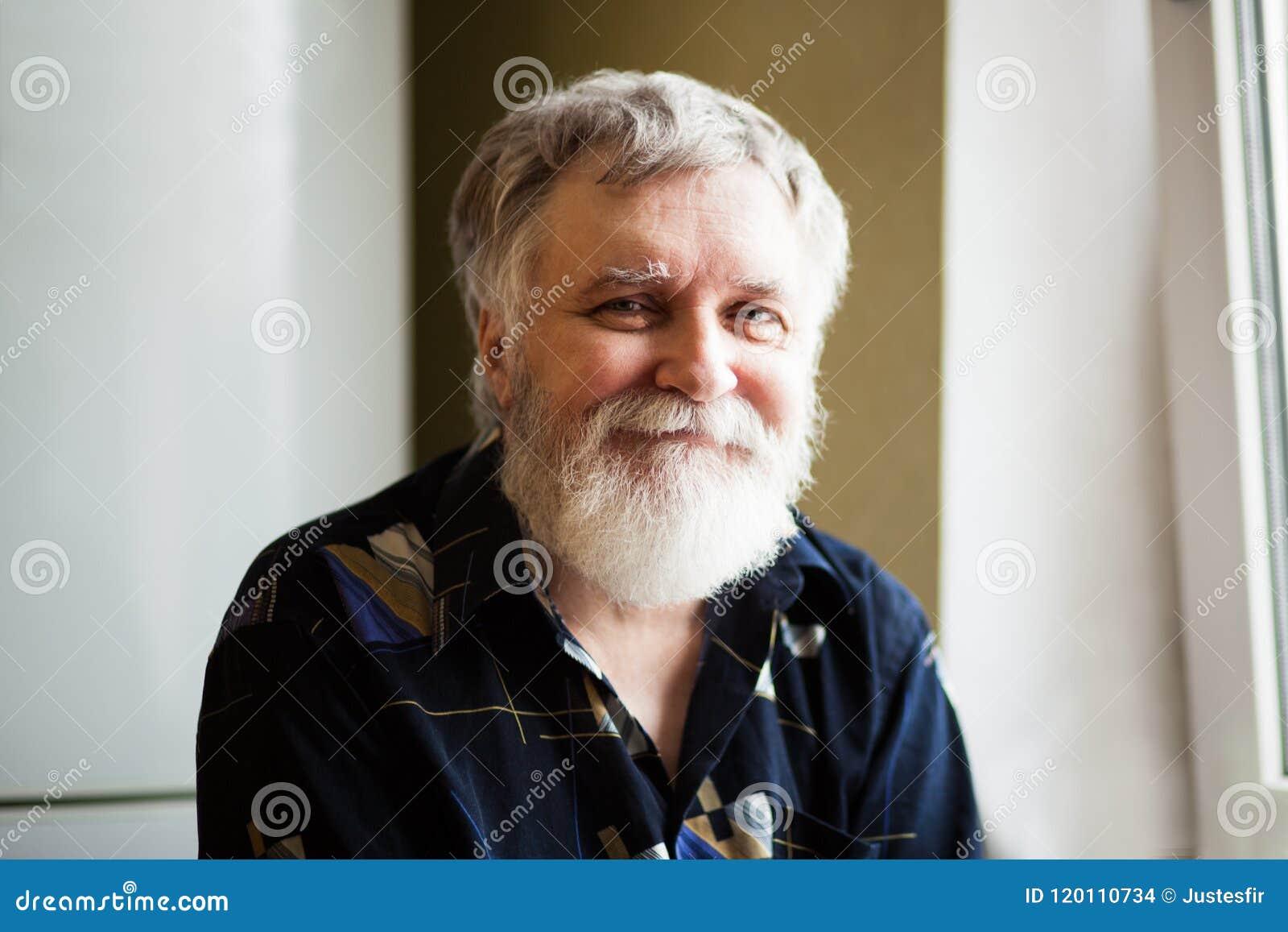 Homme adulte heureux avec les cheveux gris examinant l appareil-photo et le sourire
