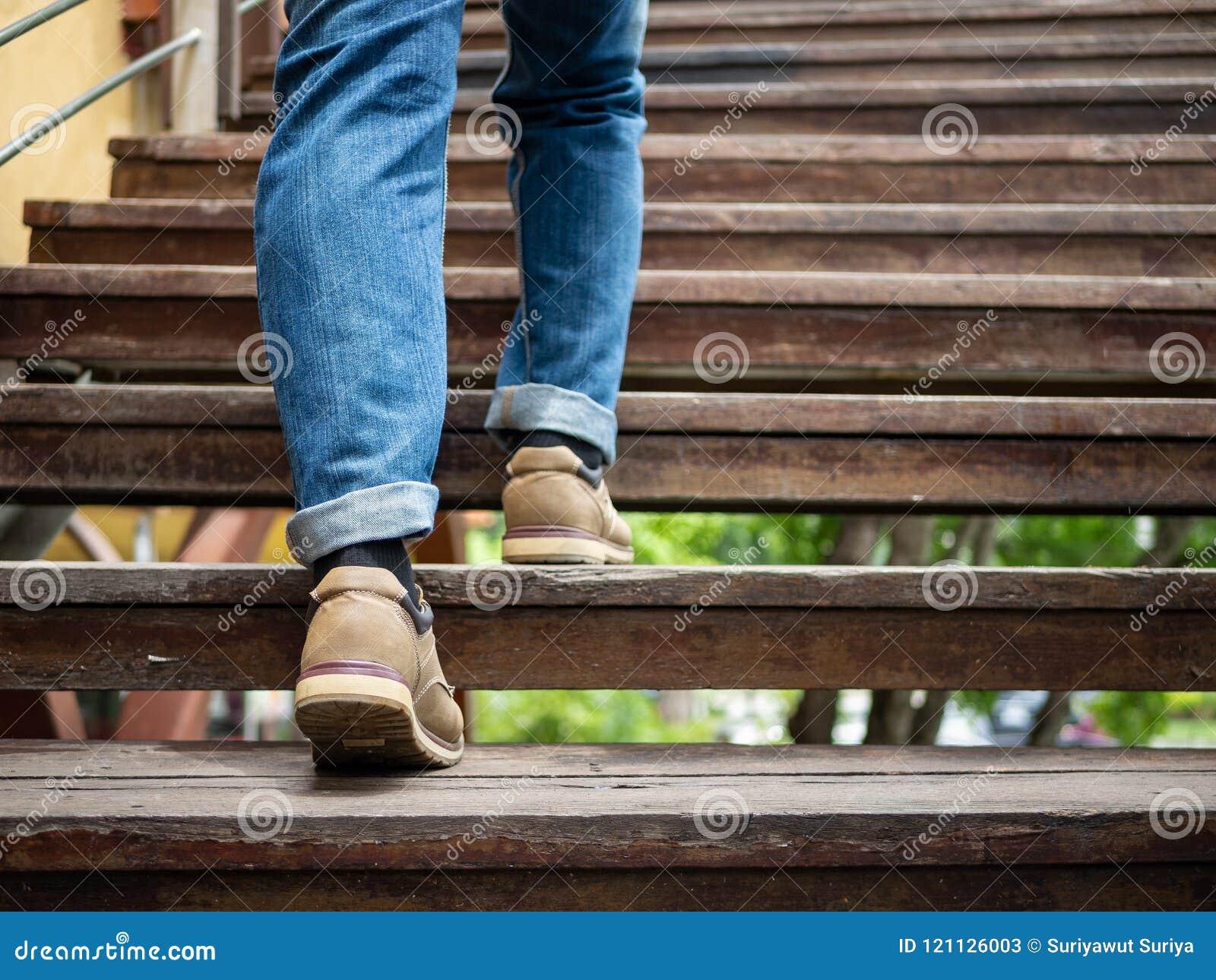 Homme adulte marchant vers le haut des escaliers en bois Faire avancer le concept