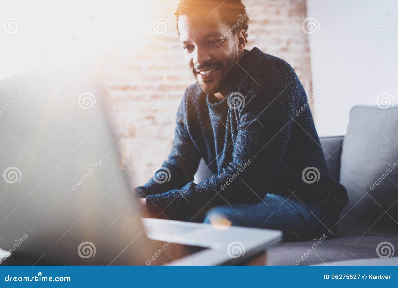 Homme africain barbu gai travaillant sur l ordinateur portable tout en reposant le sofa à son endroit moderne de bureau Concept d