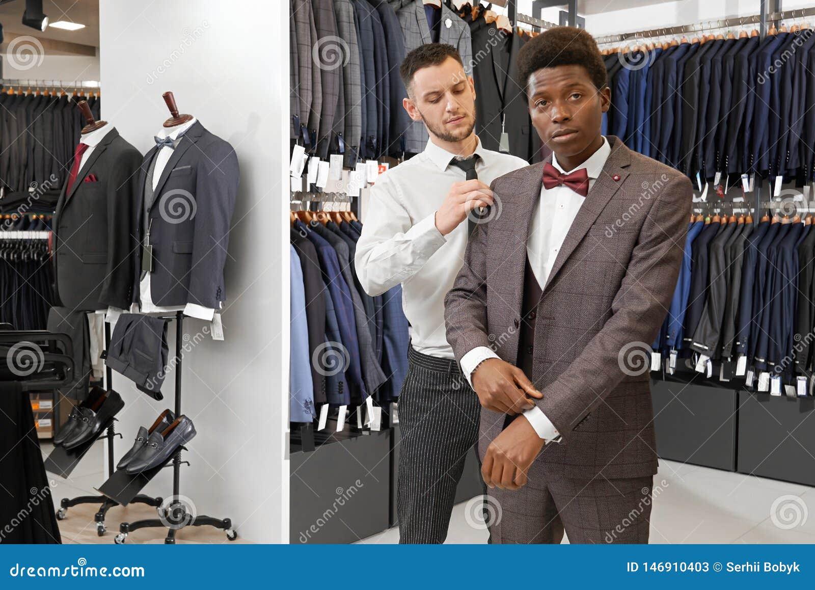 Homme africain dans la boutique essayant, choisissant le costume élégant