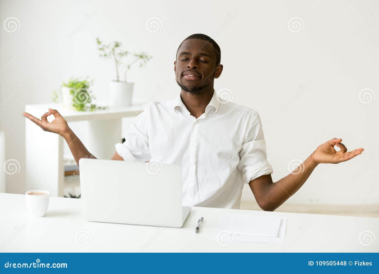 Homme africain heureux calme méditant au bureau avec l ordinateur portable