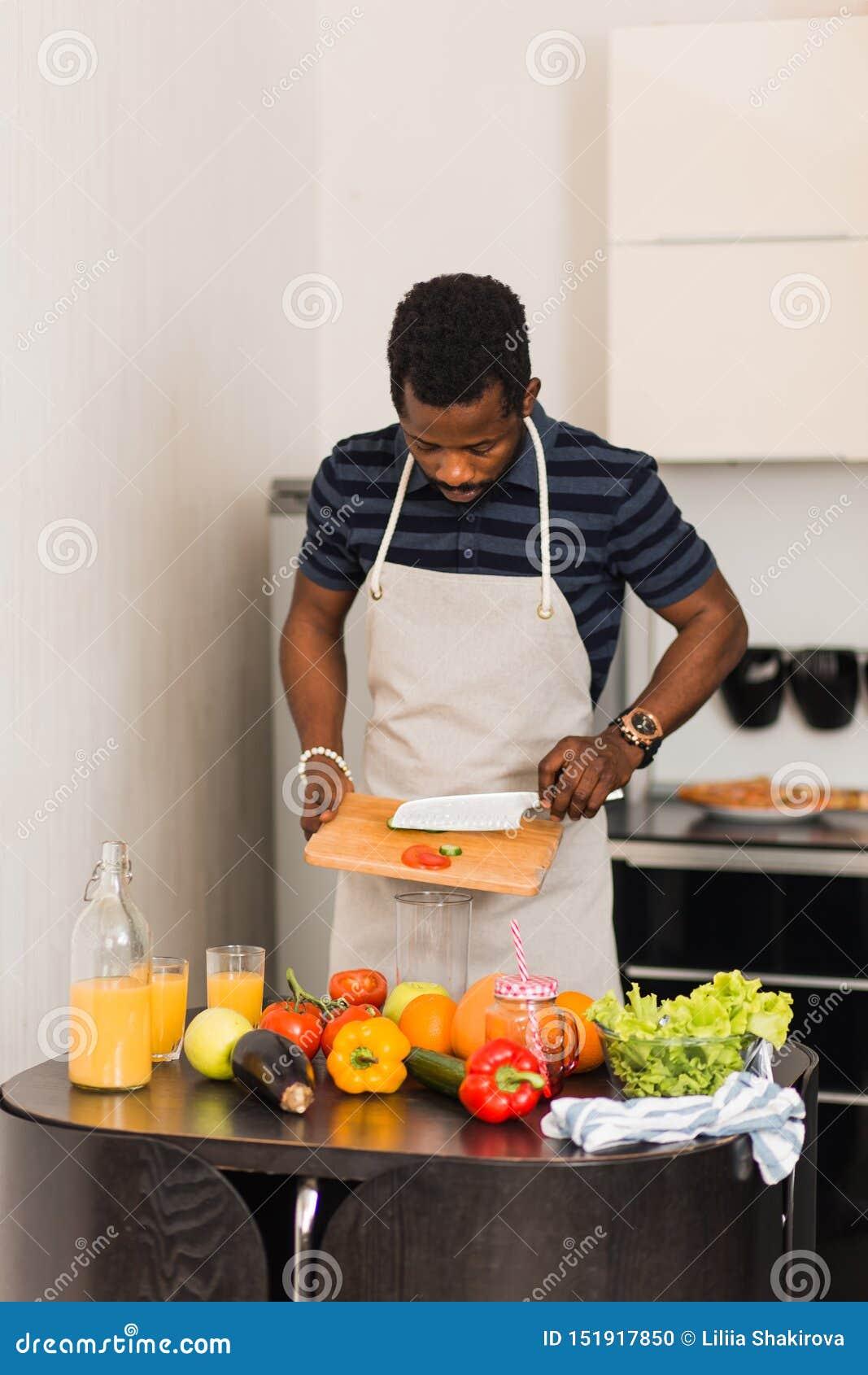 Homme africain préparant la nourriture saine à la maison dans la cuisine