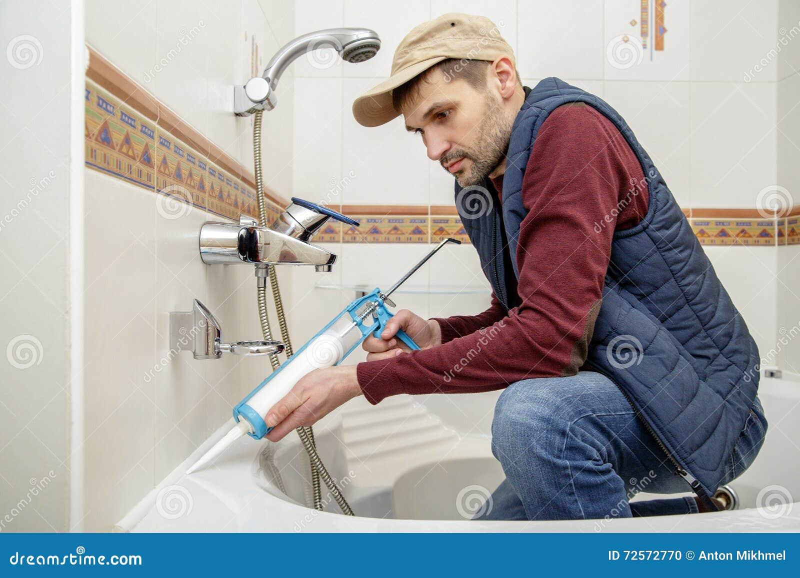 Homme appliquant le mastic de silicone dans la salle de Mastic salle de bain