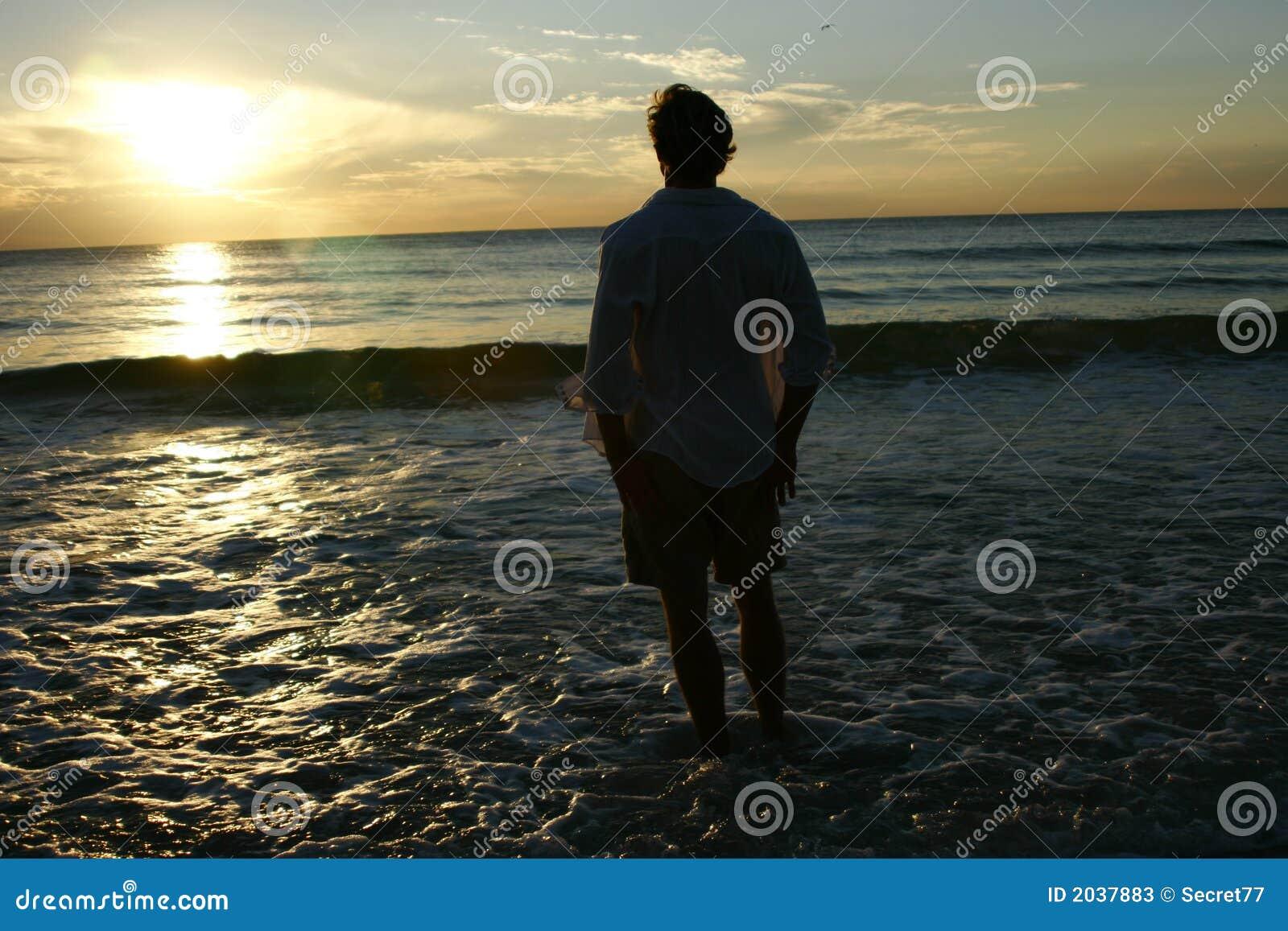 Homme appréciant le coucher du soleil