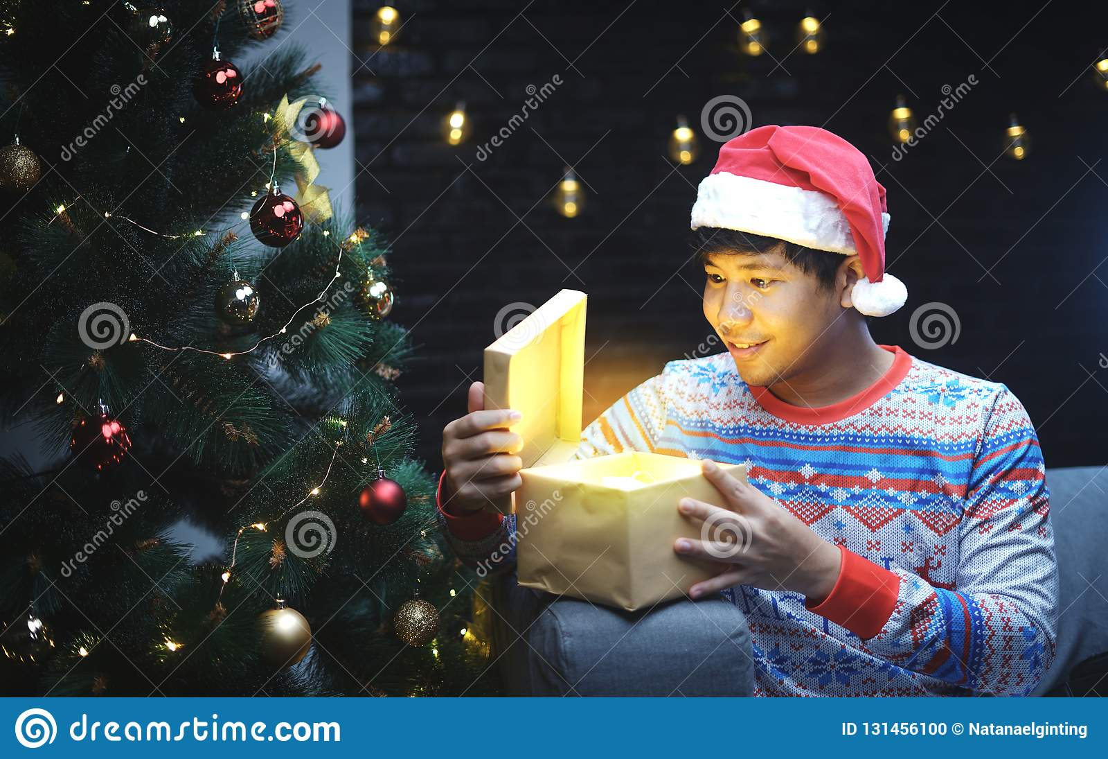 Homme asiatique avec le cadeau brillant s ouvrant de costume de Noël, se reposant près de l arbre de Noël