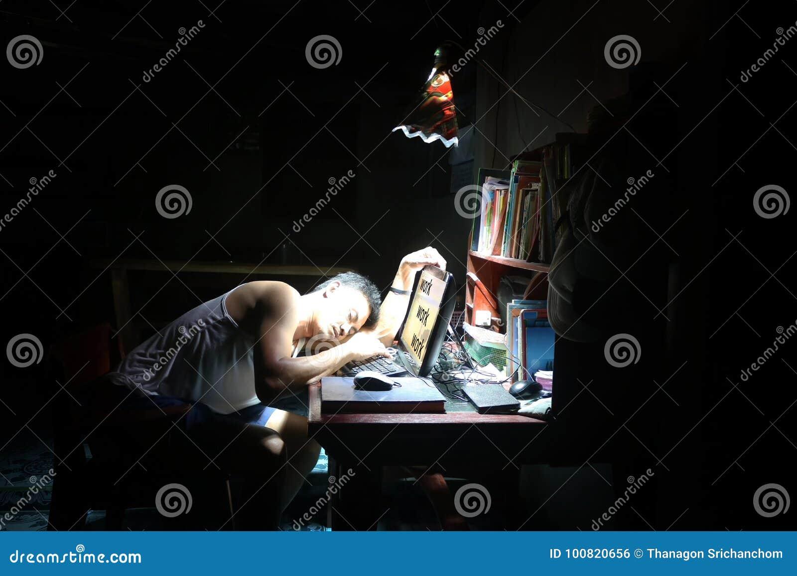 Homme asiatique dormant sur le bureau et un ordinateur dans la