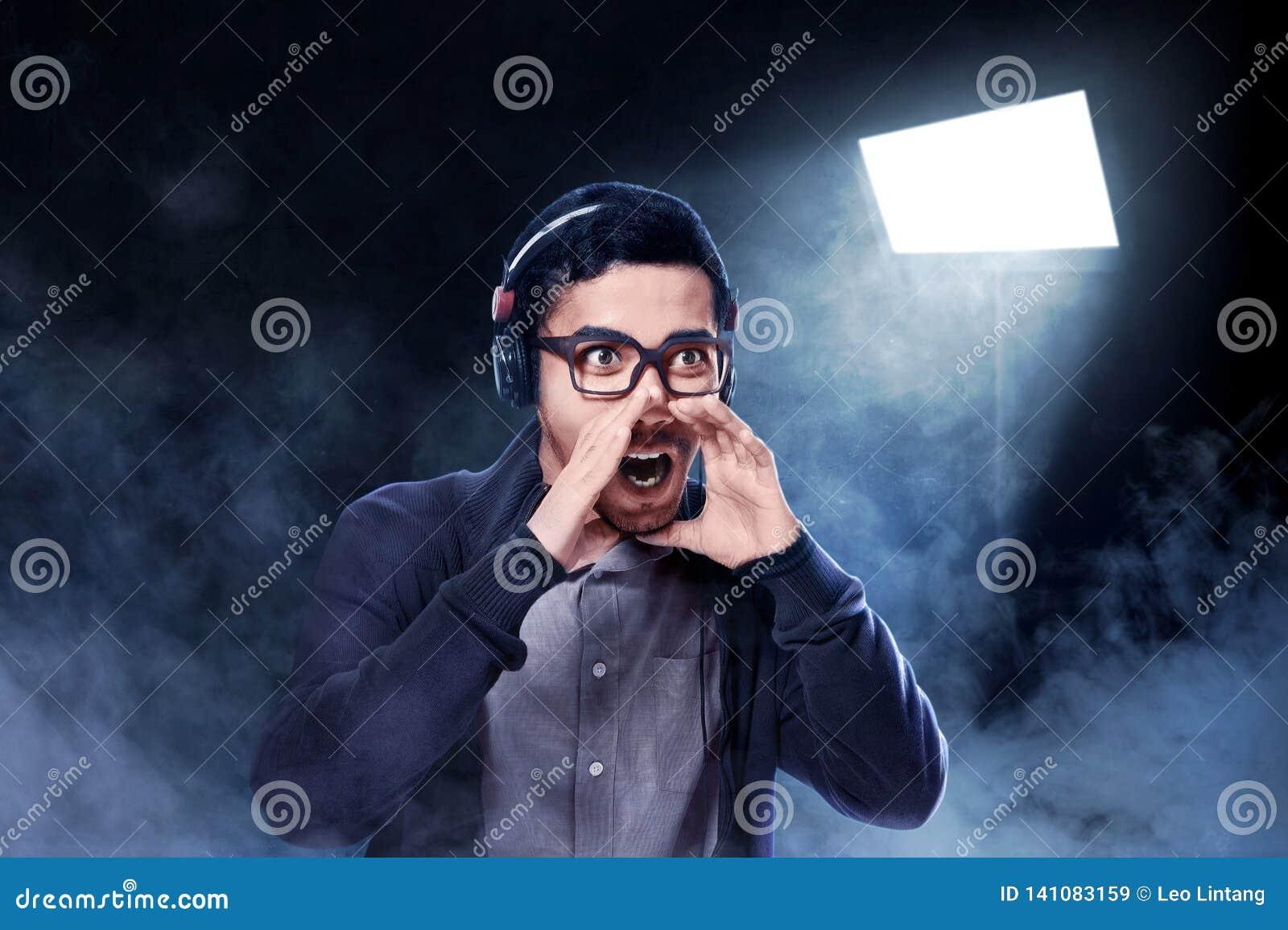 Homme asiatique expressif dans la musique de écoute de veste brune avec des écouteurs sur sa tête et apprécier la chanson