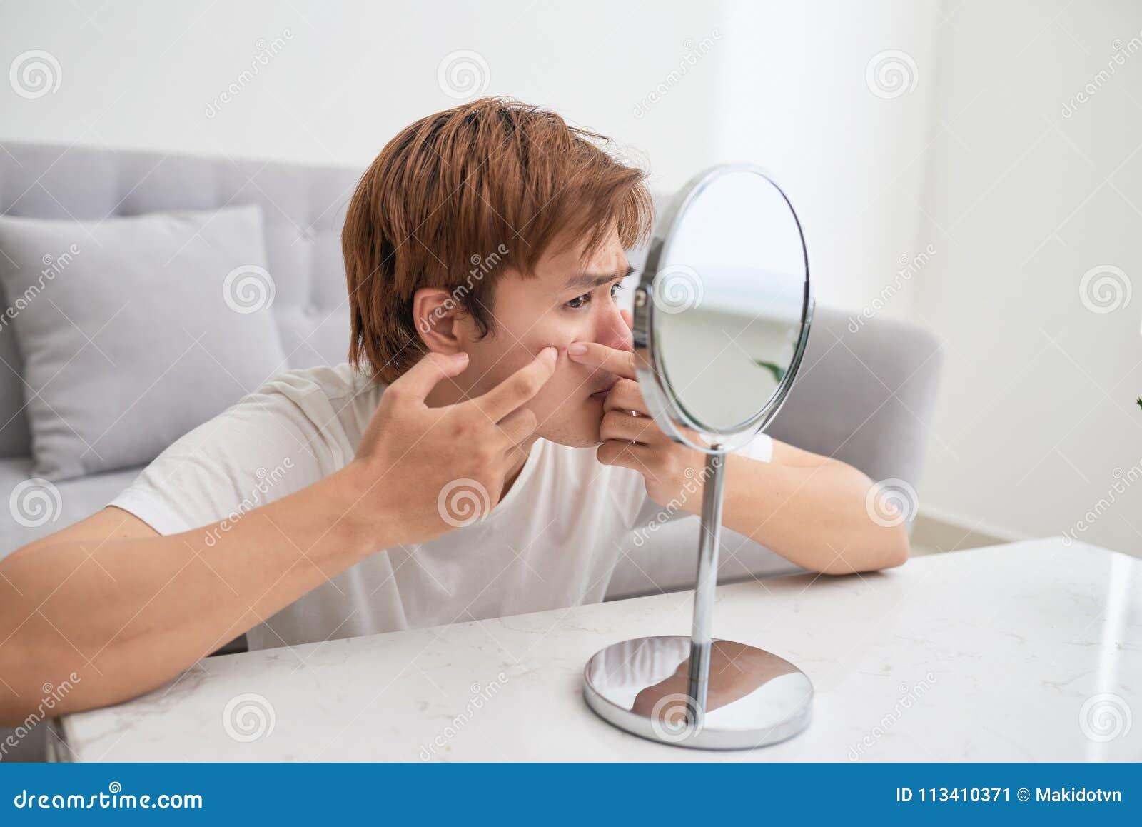 Homme asiatique regardant le miroir et sautant un bouton