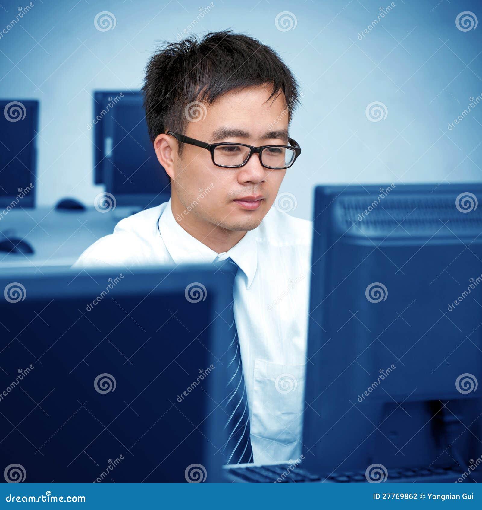 Homme asiatique travaillant dans la salle des ordinateurs