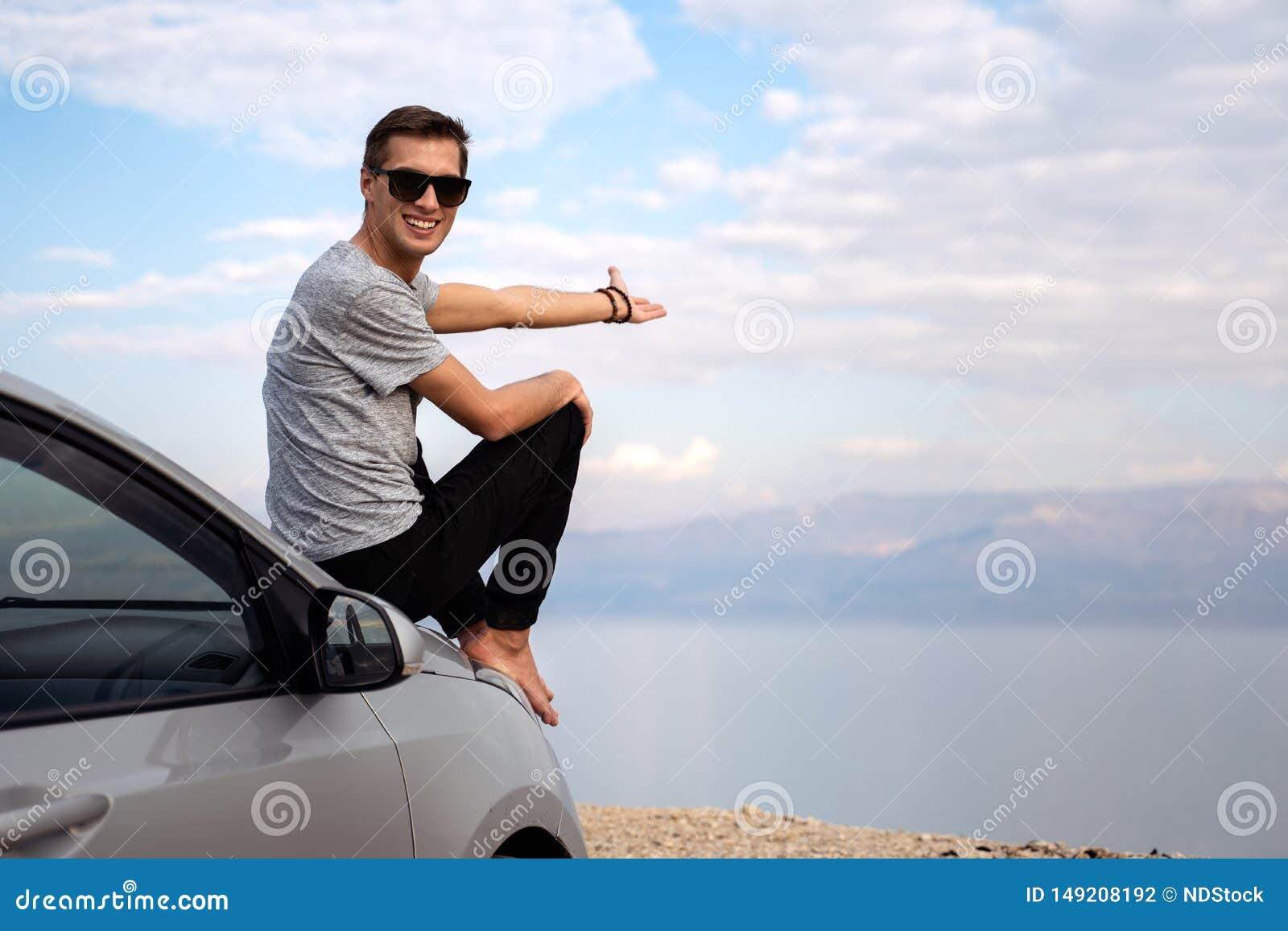 Homme assis sur le capot de moteur d une voiture lou?e sur un voyage par la route en Isra?l