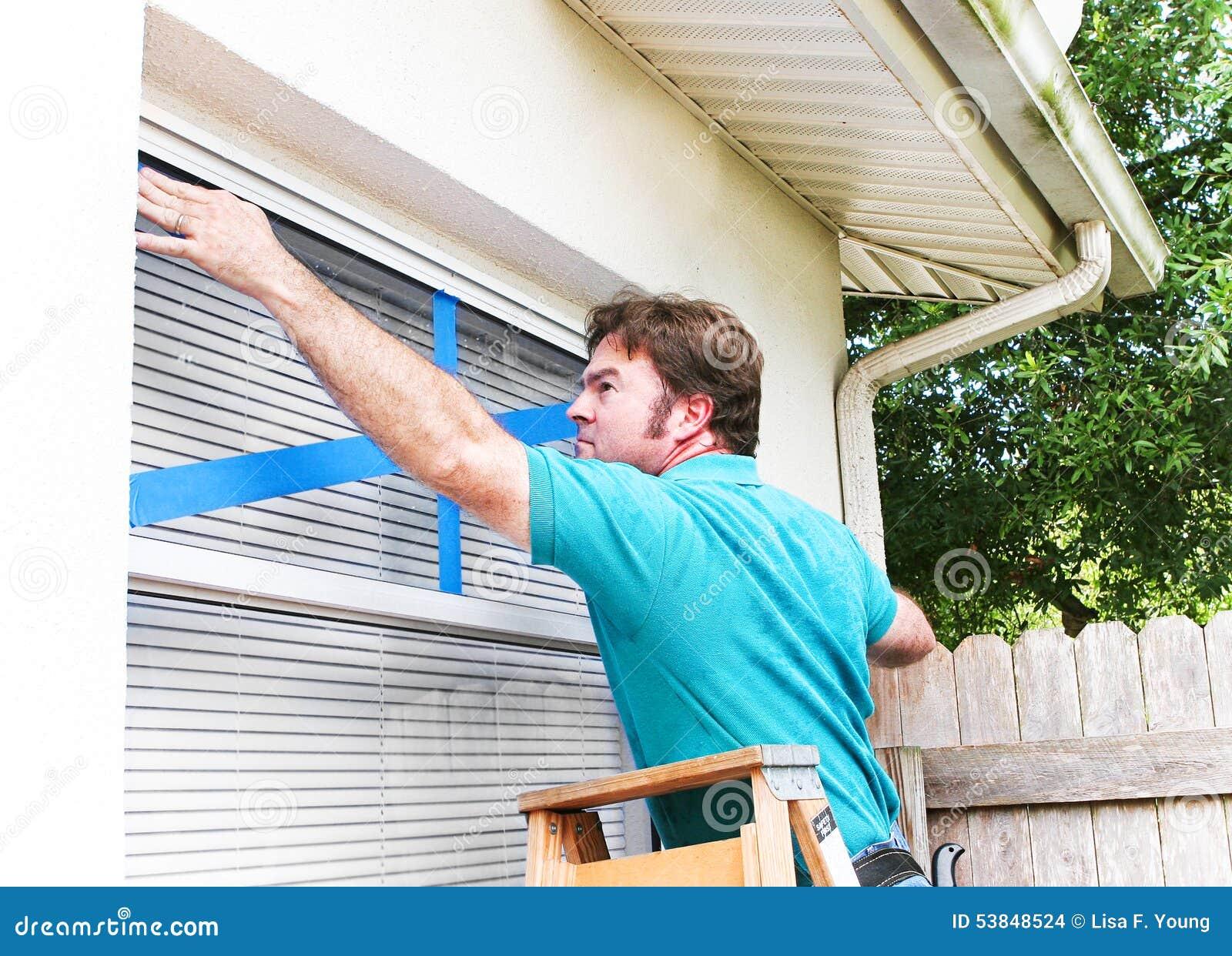 Homme attachant du ruban adhésif à son Windows