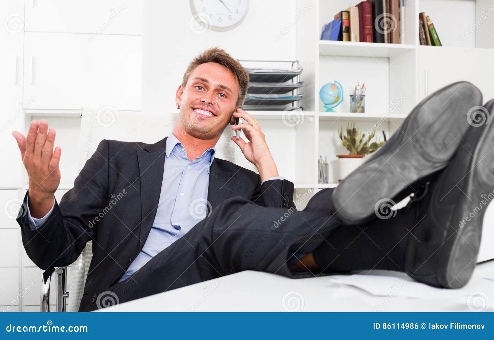 Image bureau libre de parler au tÉlÉphone avec ses pieds sur le