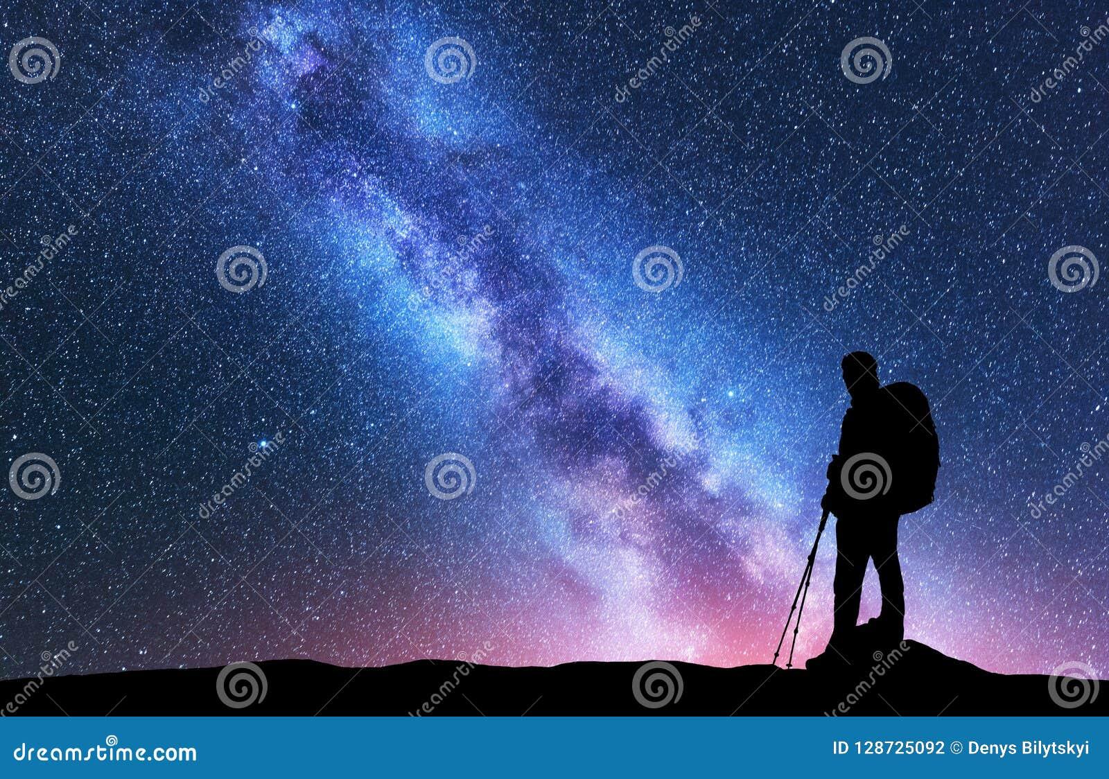 Homme avec des poteaux de sac à dos et de trekking contre la manière laiteuse