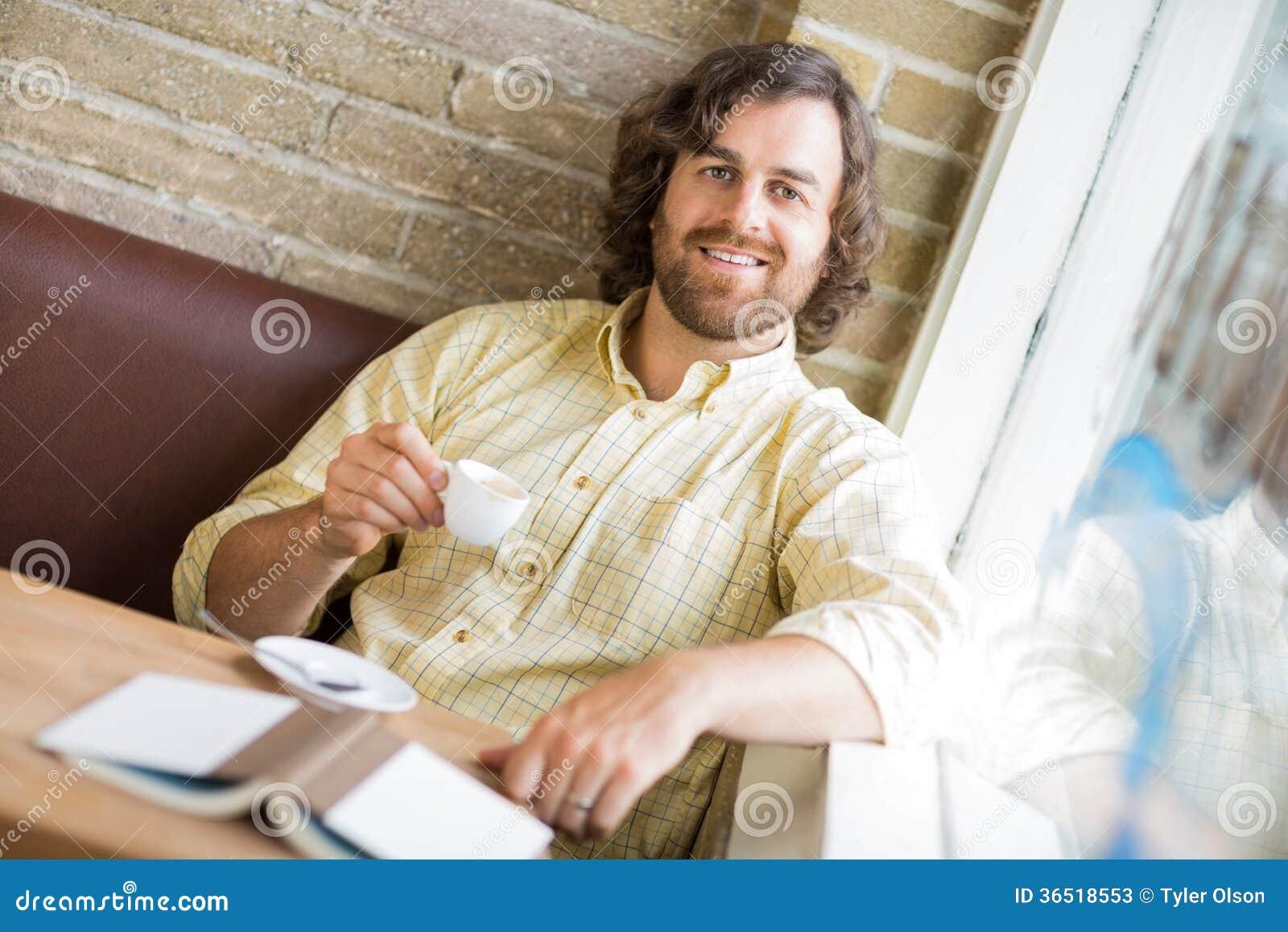 Homme avec la tasse et le livre de café en café