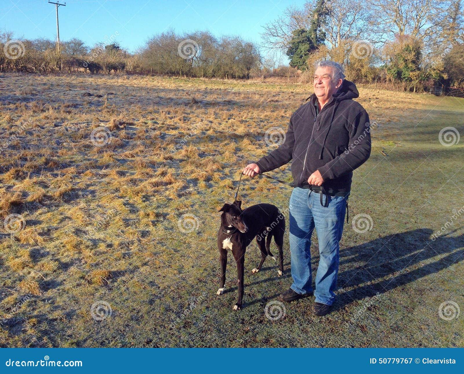 homme avec le chien de l vrier sur une laisse photo stock image 50779767. Black Bedroom Furniture Sets. Home Design Ideas