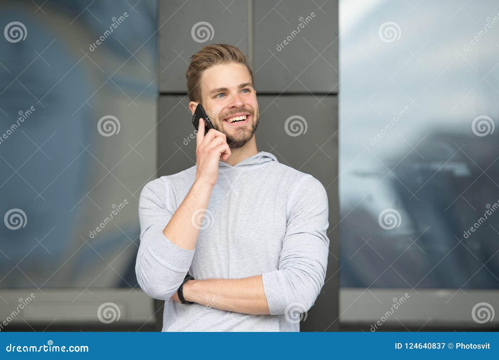 Homme avec le fond urbain de smartphone d appel de barbe Smartphone heureux d utilisation de sourire de type pour communiquer des