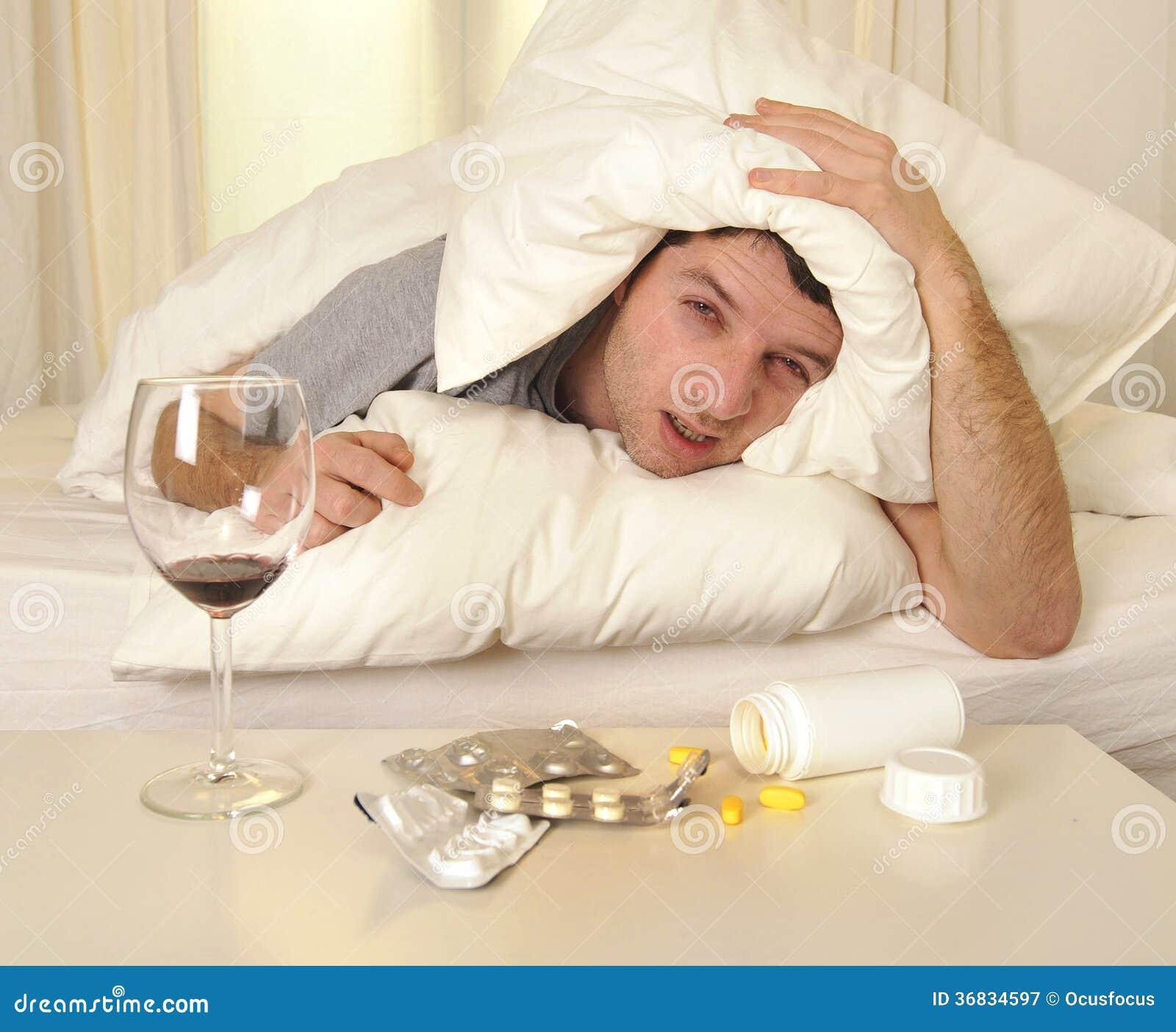 homme avec le mal de t te et la gueule de bois dans le lit avec des comprim s image stock. Black Bedroom Furniture Sets. Home Design Ideas