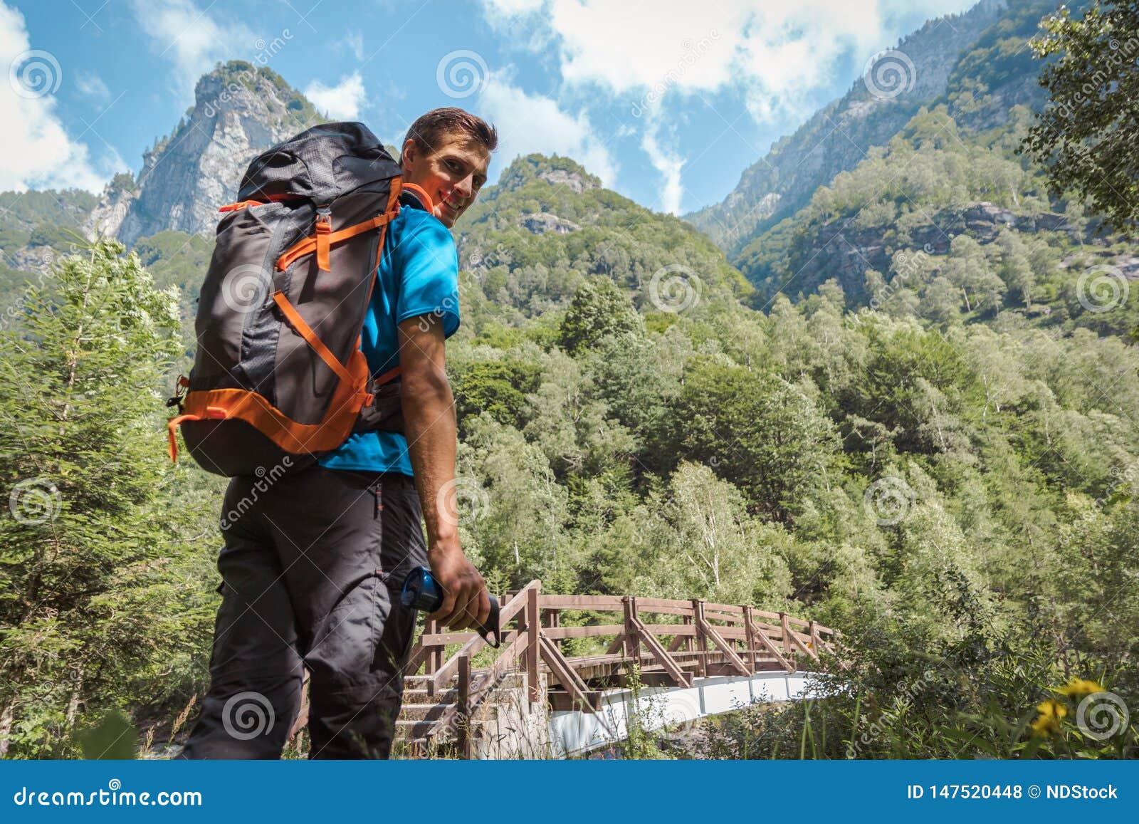 Homme avec le sac à dos souriant à la caméra entourée par la nature et les montagnes étonnantes