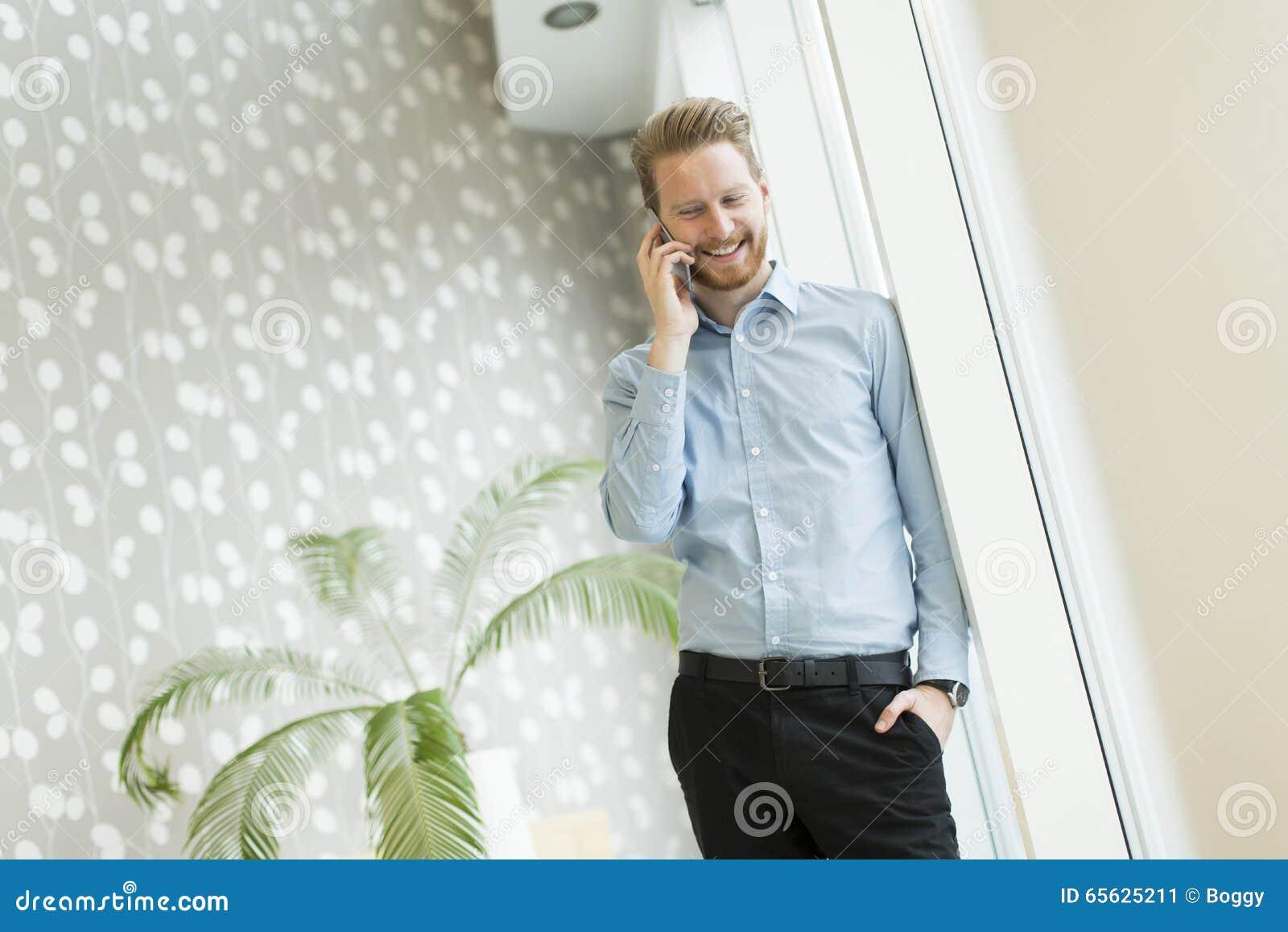 Homme avec le téléphone portable dans le bureau