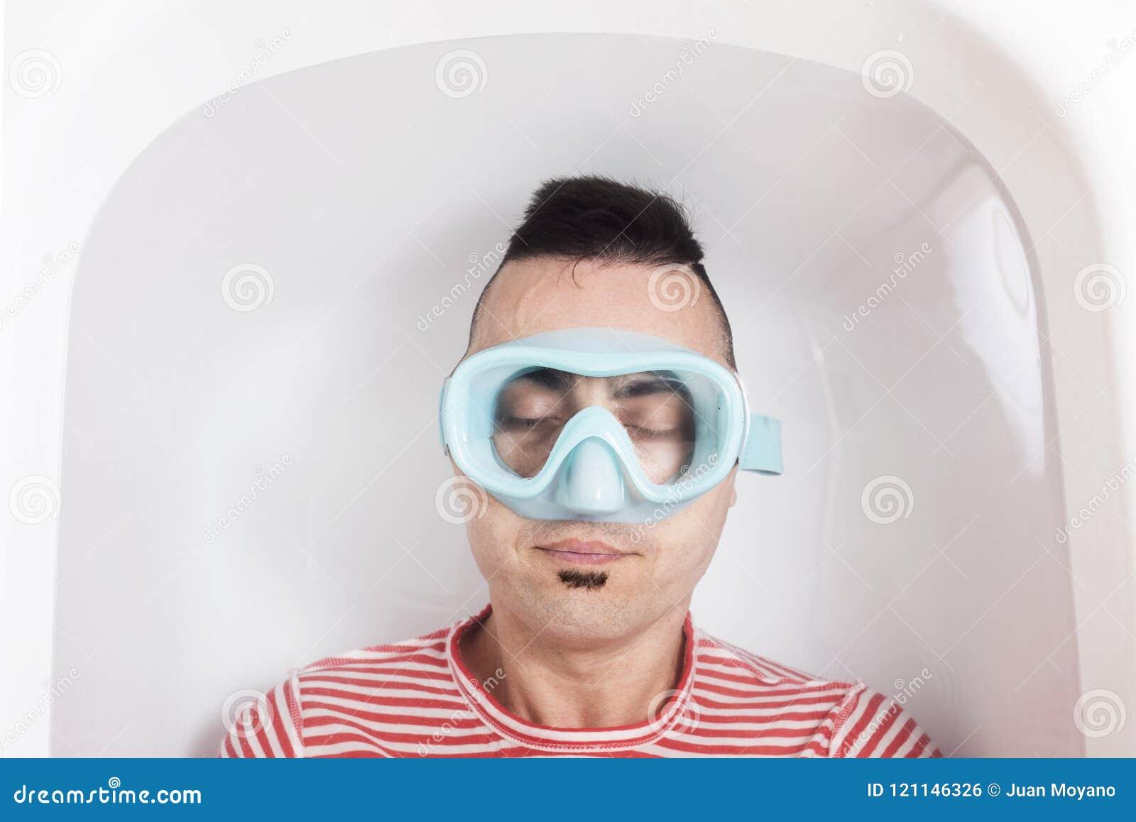 homme-avec-un-masque-de-plong%C3%A9e-dans-l-eau-d-une-baignoire-121146326