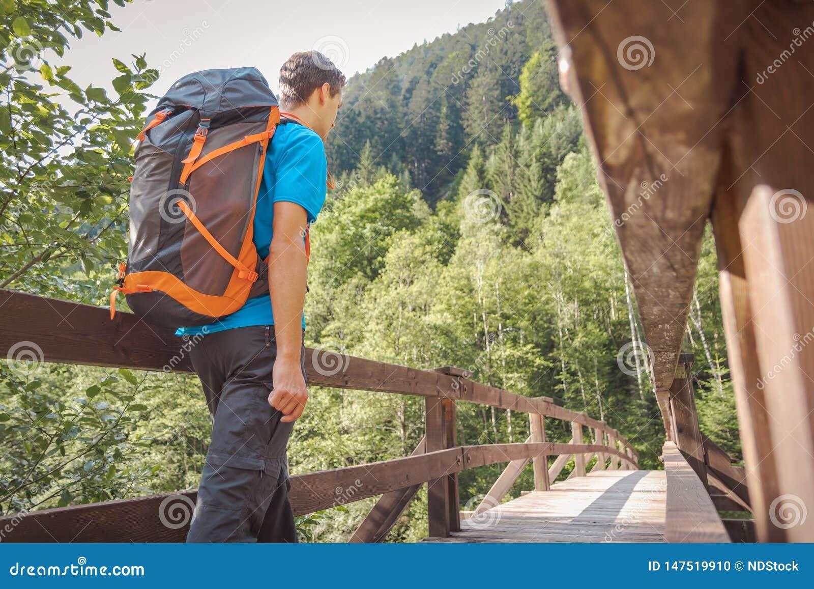 Homme avec un sac ? dos entrant sur un pont dans la for?t