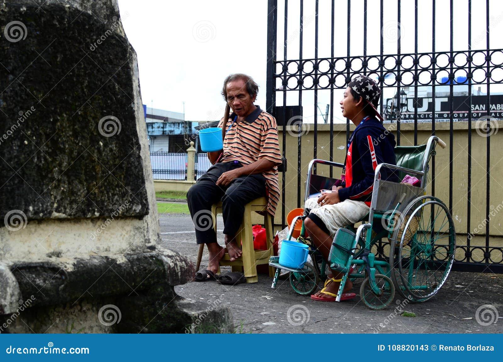 Homme aveugle près de mendiant handicapé dans le fauteuil roulant au portail de porte de yard d église pour chercher l aumône