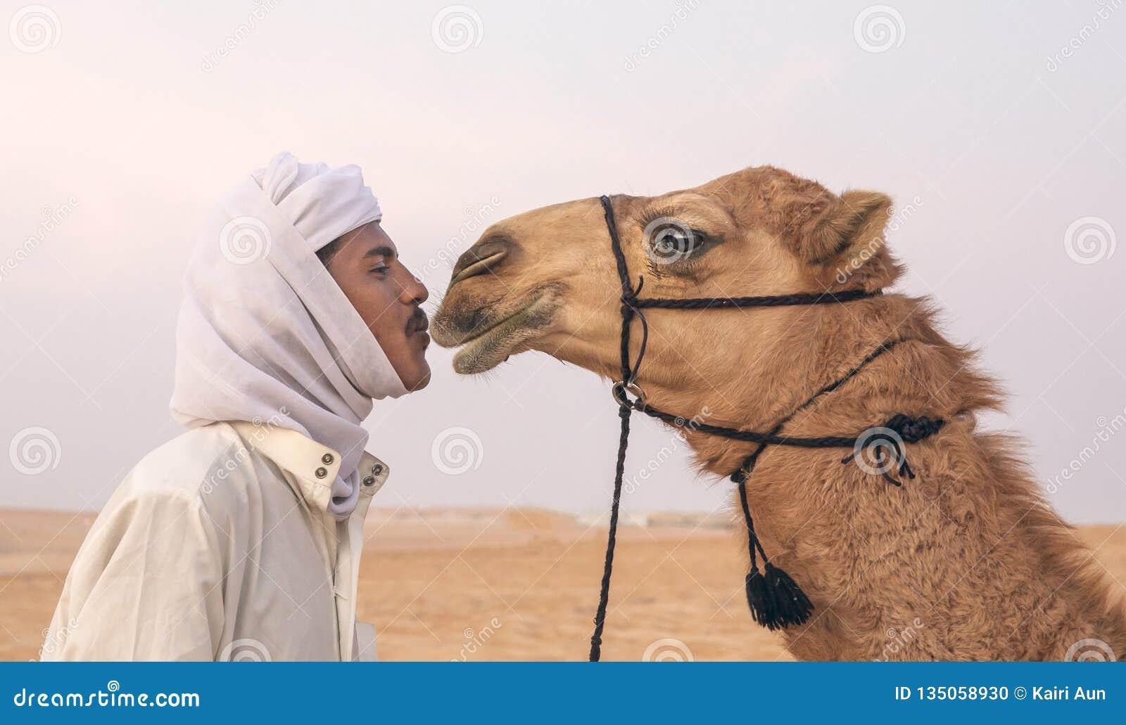 Homme bédouin embrassant son chameau