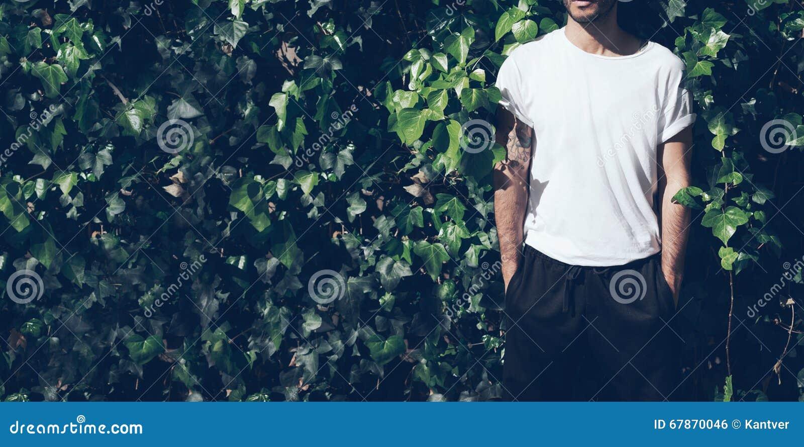 Homme barbu avec le tatouage utilisant le T-shirt blanc vide et les lunettes de soleil noires Fond vert de mur de jardin Plan rap