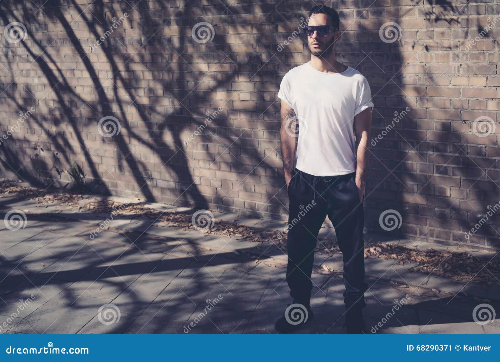 Homme barbu avec le tatouage utilisant le T-shirt blanc vide Supports devant un mur de briques Fond de rue de ville horizontal