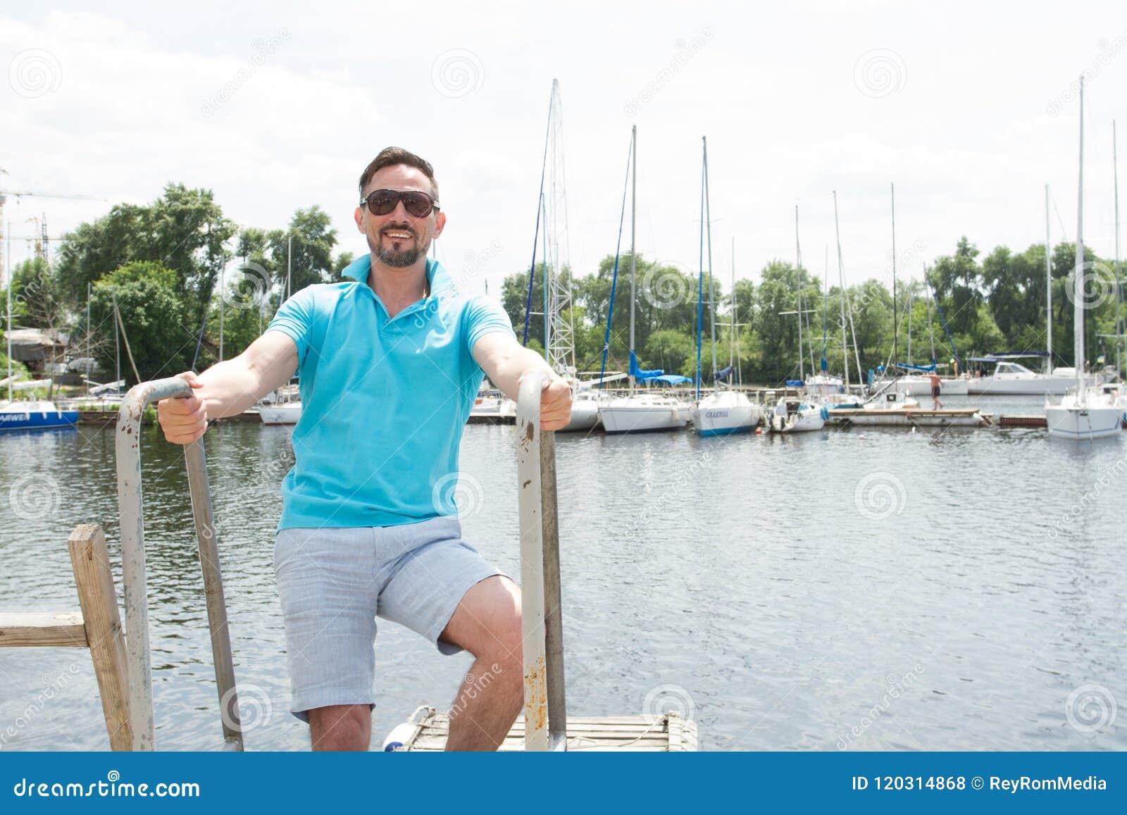Homme barbu dans le polo et lunettes de soleil laddering sur le bateau Homme d affaires heureux des vacances avec des yachts sur