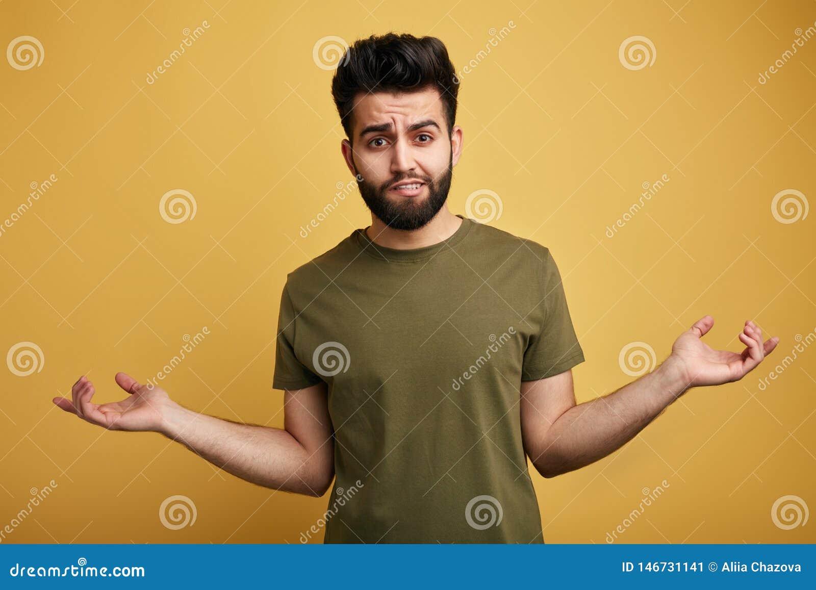 Homme barbu douteux incertain utilisant le T-shirt vert gesticulant ses épaules