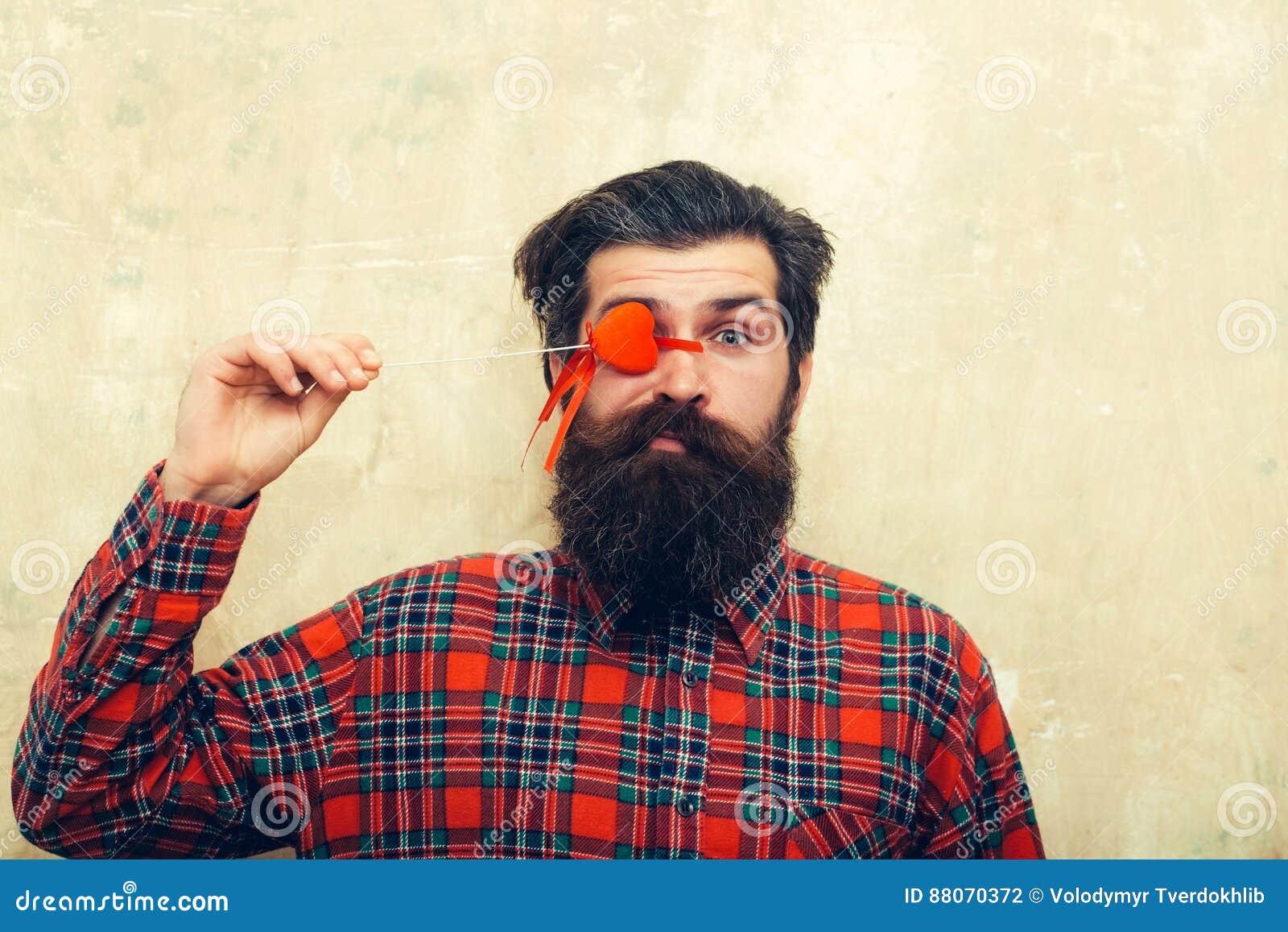 Homme barbu drôle tenant le coeur rouge sur le bâton avant oeil