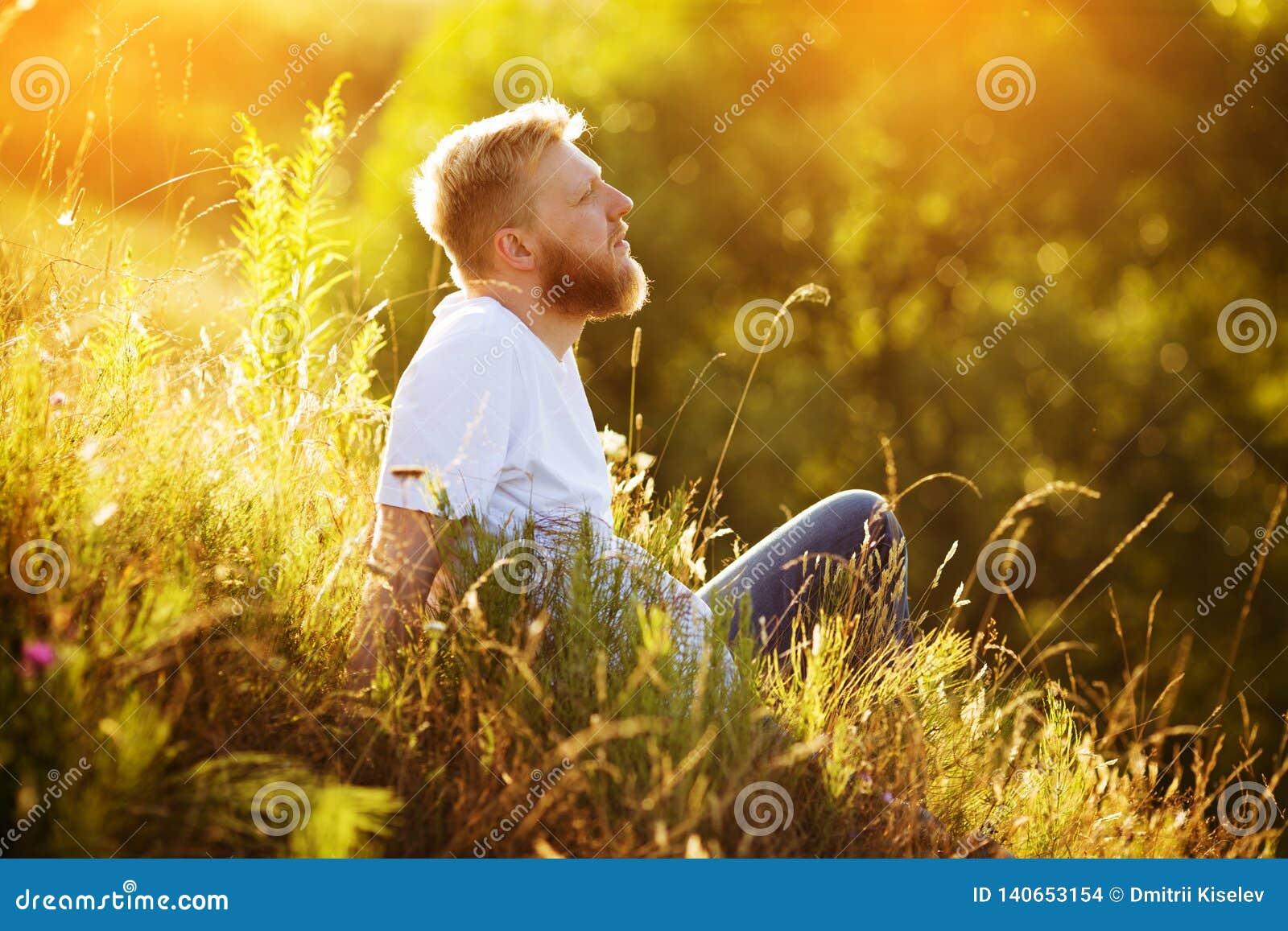 Homme barbu heureux se reposant parmi des wildflowers