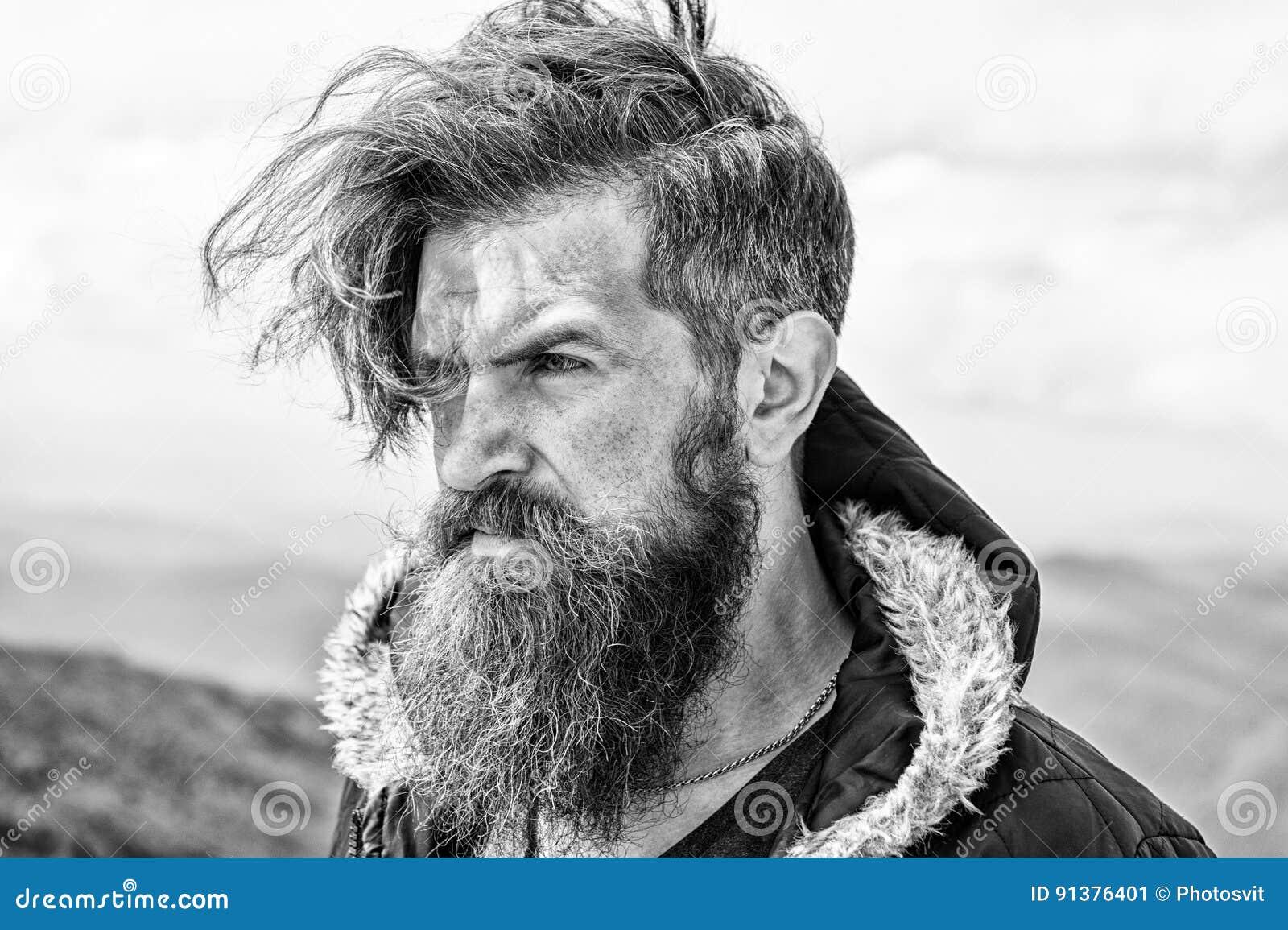Homme barbu sur le dessus venteux de montagne sur le ciel nuageux naturel