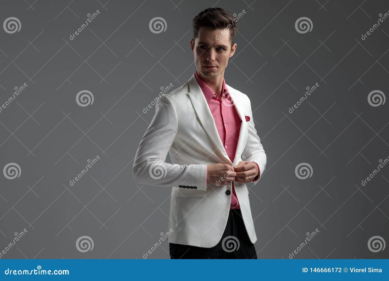 Homme bel boutonnant sa veste de salon tout en regardant loin