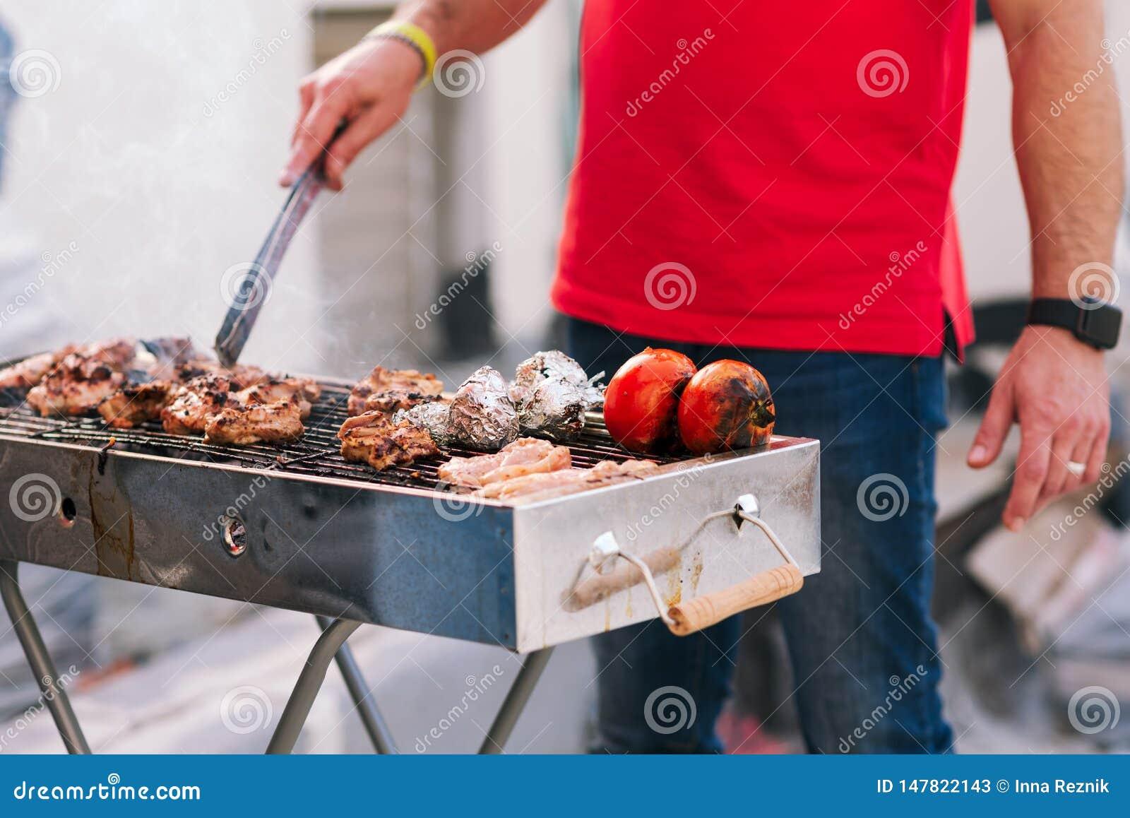 Homme bel pr?parant le barbecue pour des amis Main de jeune homme grillant une certains viande et l?gume