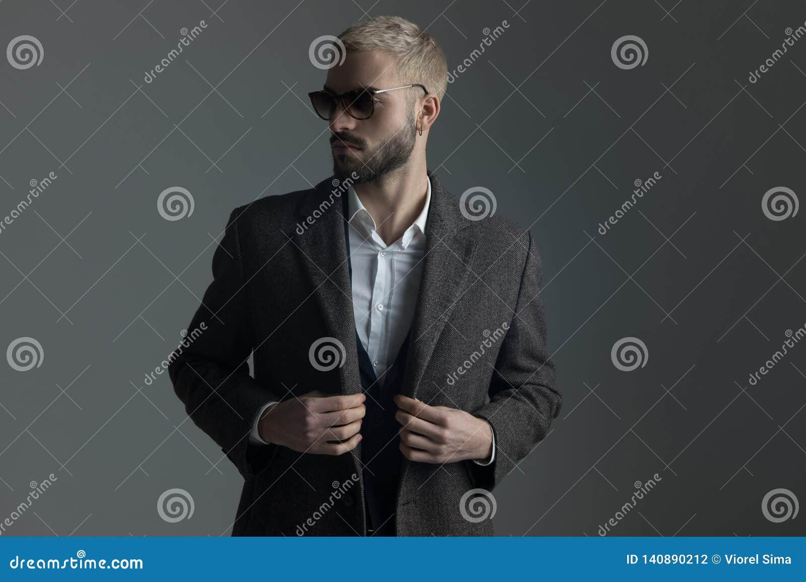Homme blond dans le costume avec des lunettes de soleil ajustant son longcoat