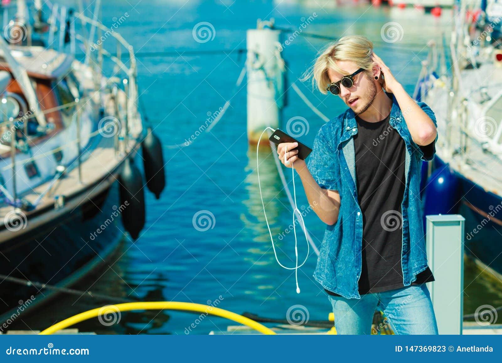 Homme blond dehors utilisant son smartphone