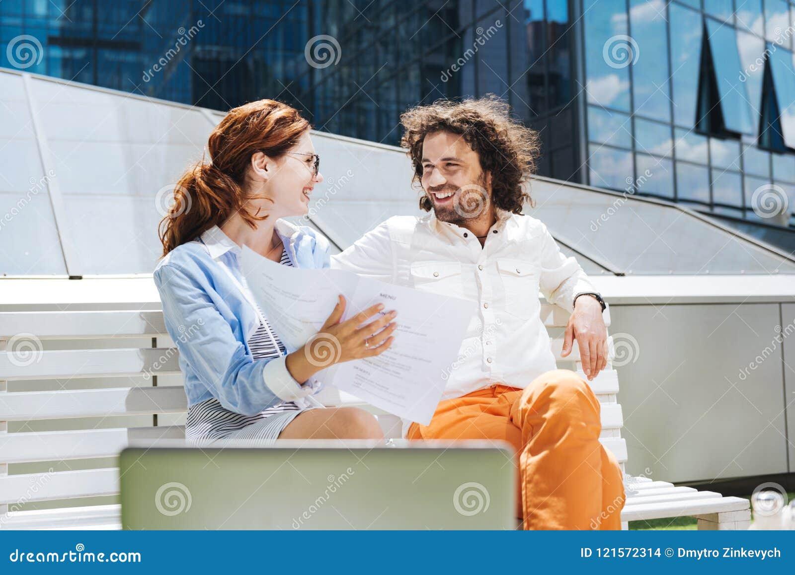 Homme bouclé barbu souriant tout en parlant à sa belle femme