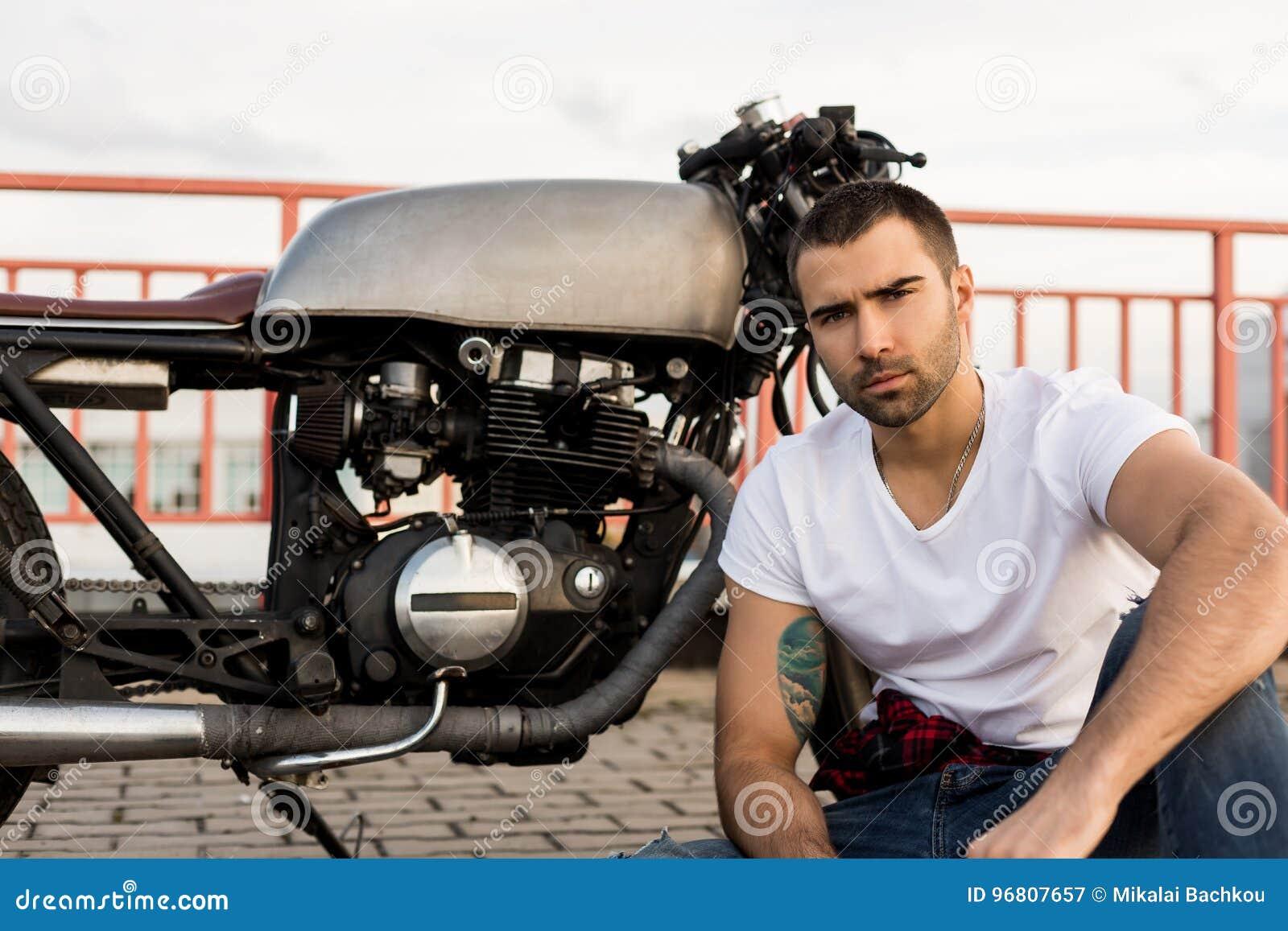 Homme brutal près de sa motocyclette de coutume de coureur de café
