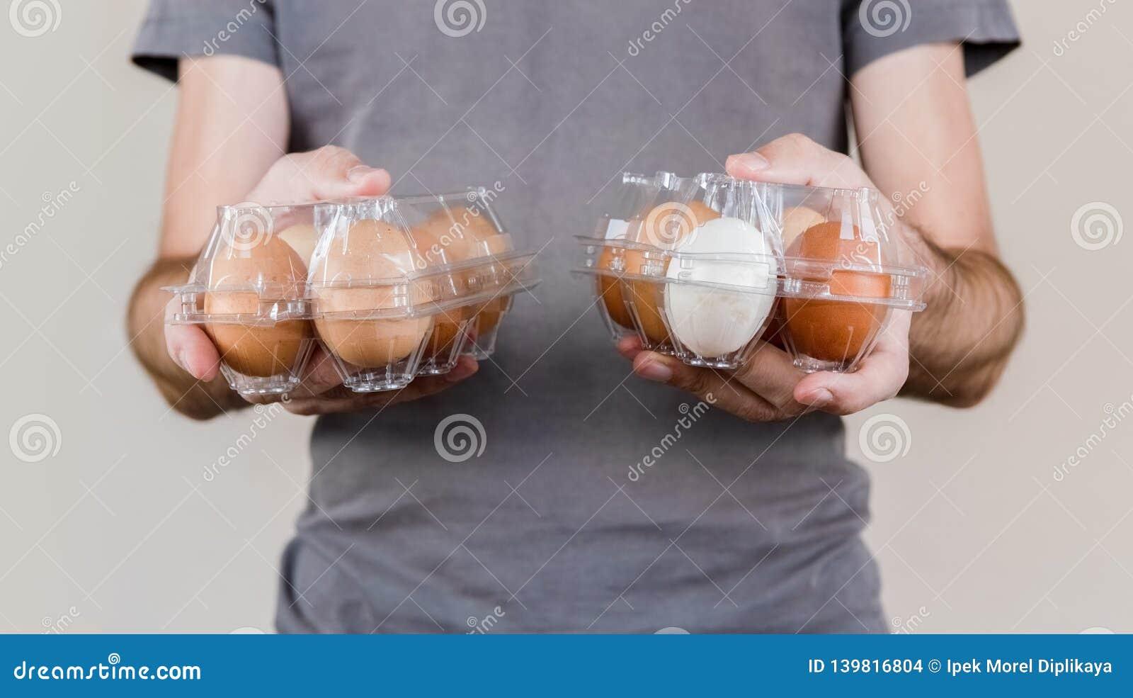 Homme caucasien avec le T-shirt gris jugeant deux boîtes à oeufs en plastique pleines des oeufs de poulet