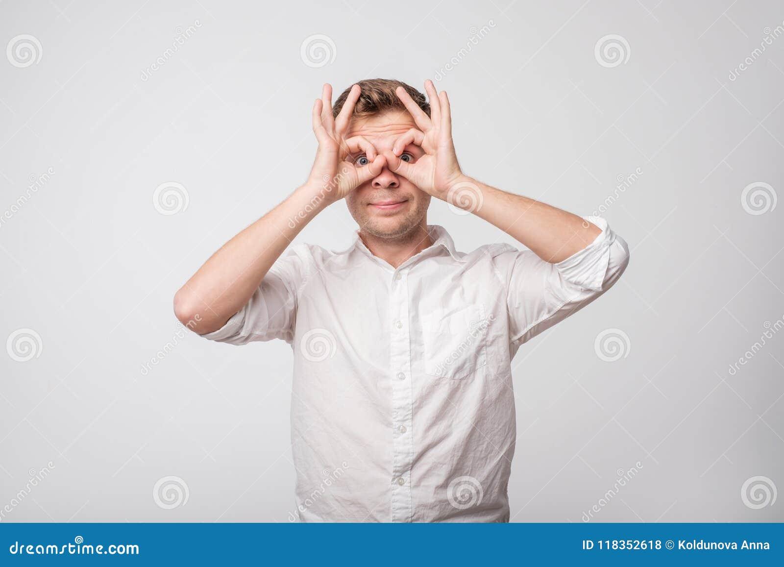 Homme caucasien faisant le signe du hibou avec des mains