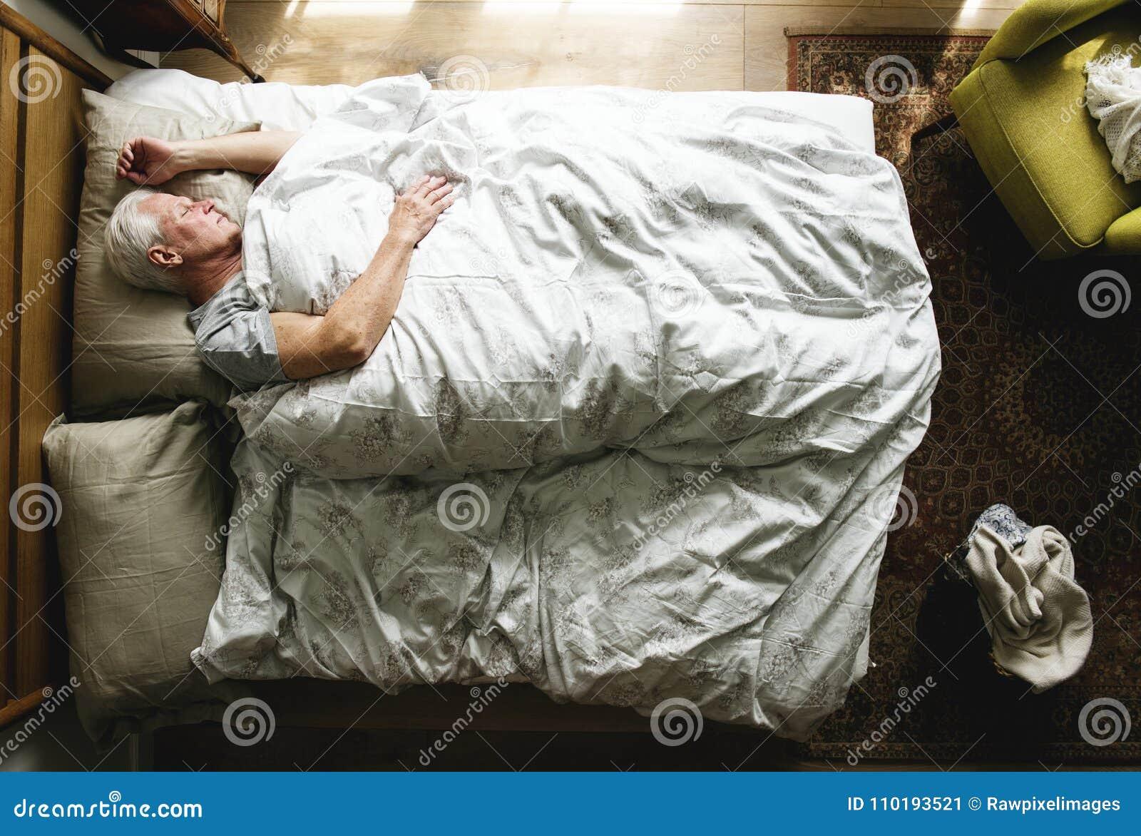 Homme caucasien plus âgé dormant sur le lit